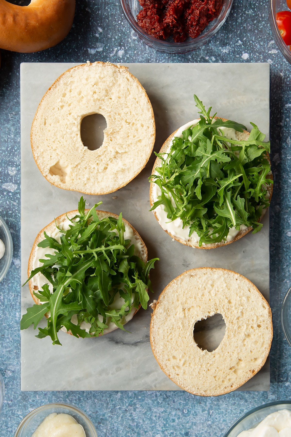 Sliced open bagels on a marble board. Half are spread with mayo and topped with rocket. Ingredients to make halloumi bagels surround the board.