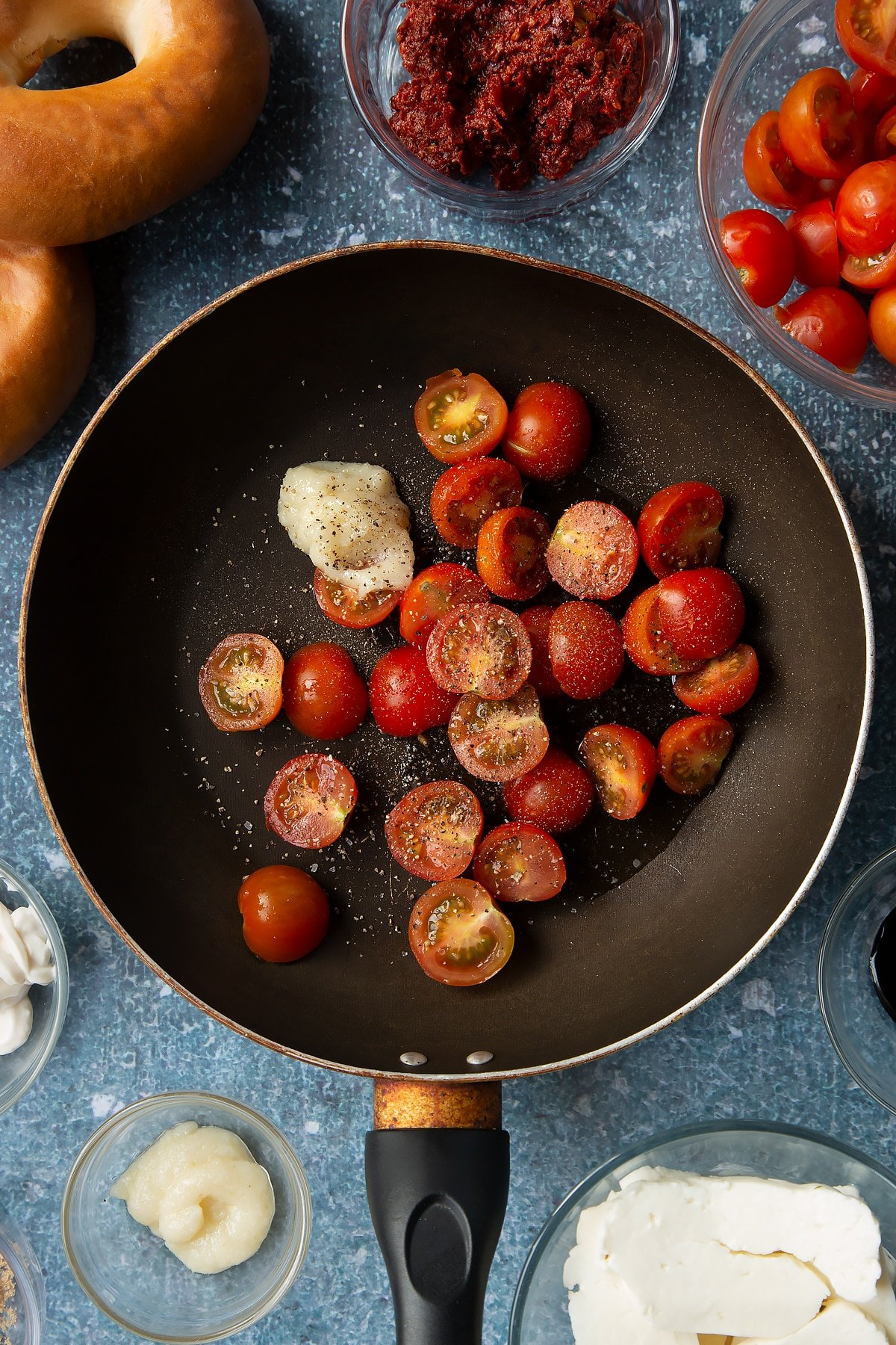 Oil, cherry tomatoes, garlic and pepper in a frying pan. Ingredients to make halloumi bagels surround the pan.