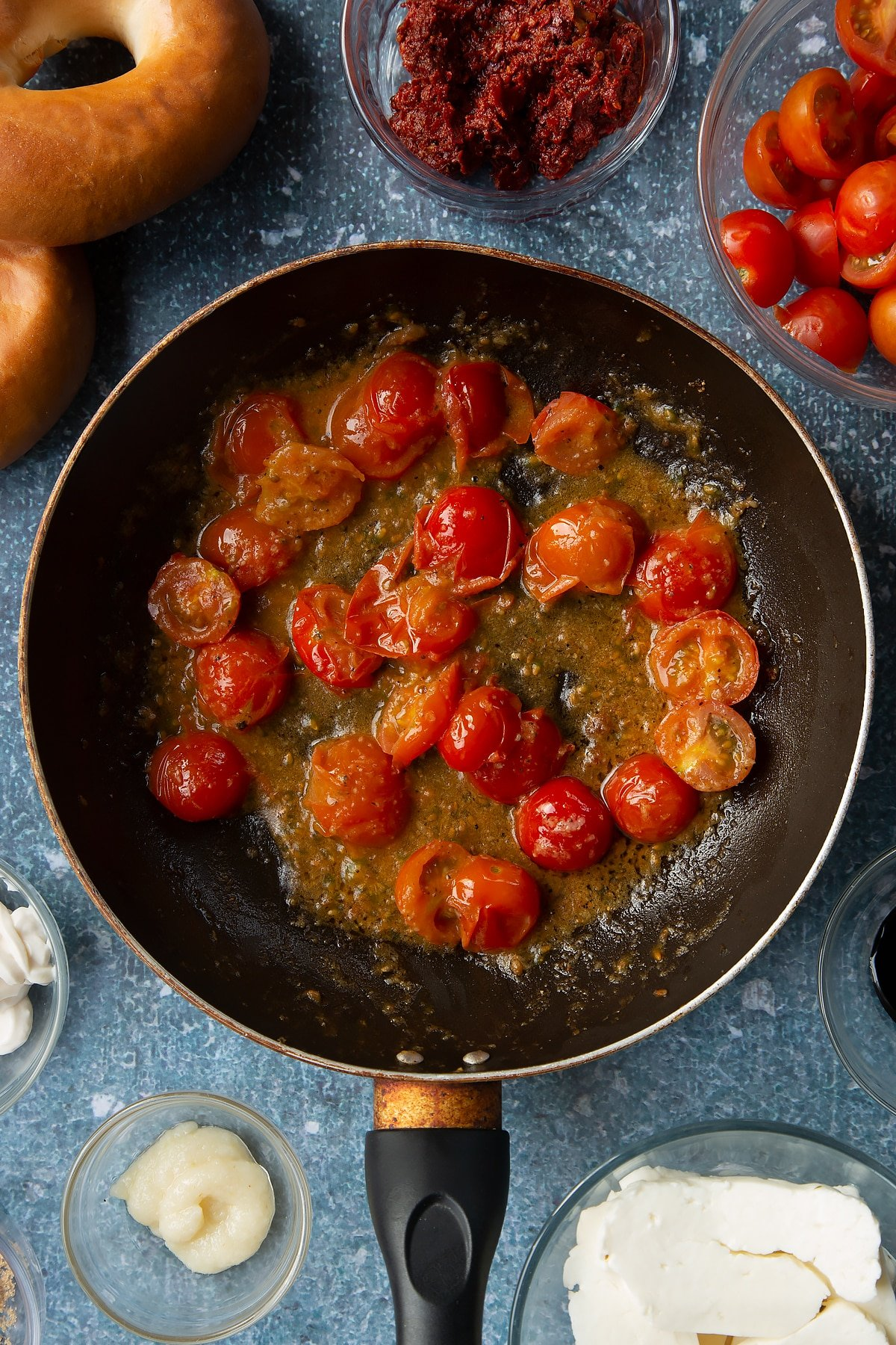 Fried down cherry tomatoes, garlic and pepper in a frying pan. Ingredients to make halloumi bagels surround the pan.