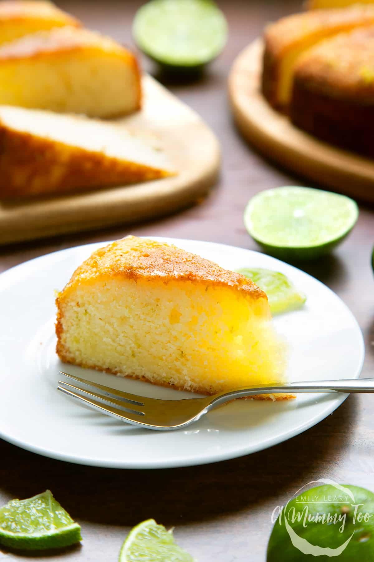 Slice of lime drizzle cake standing on a white plate with a fork.