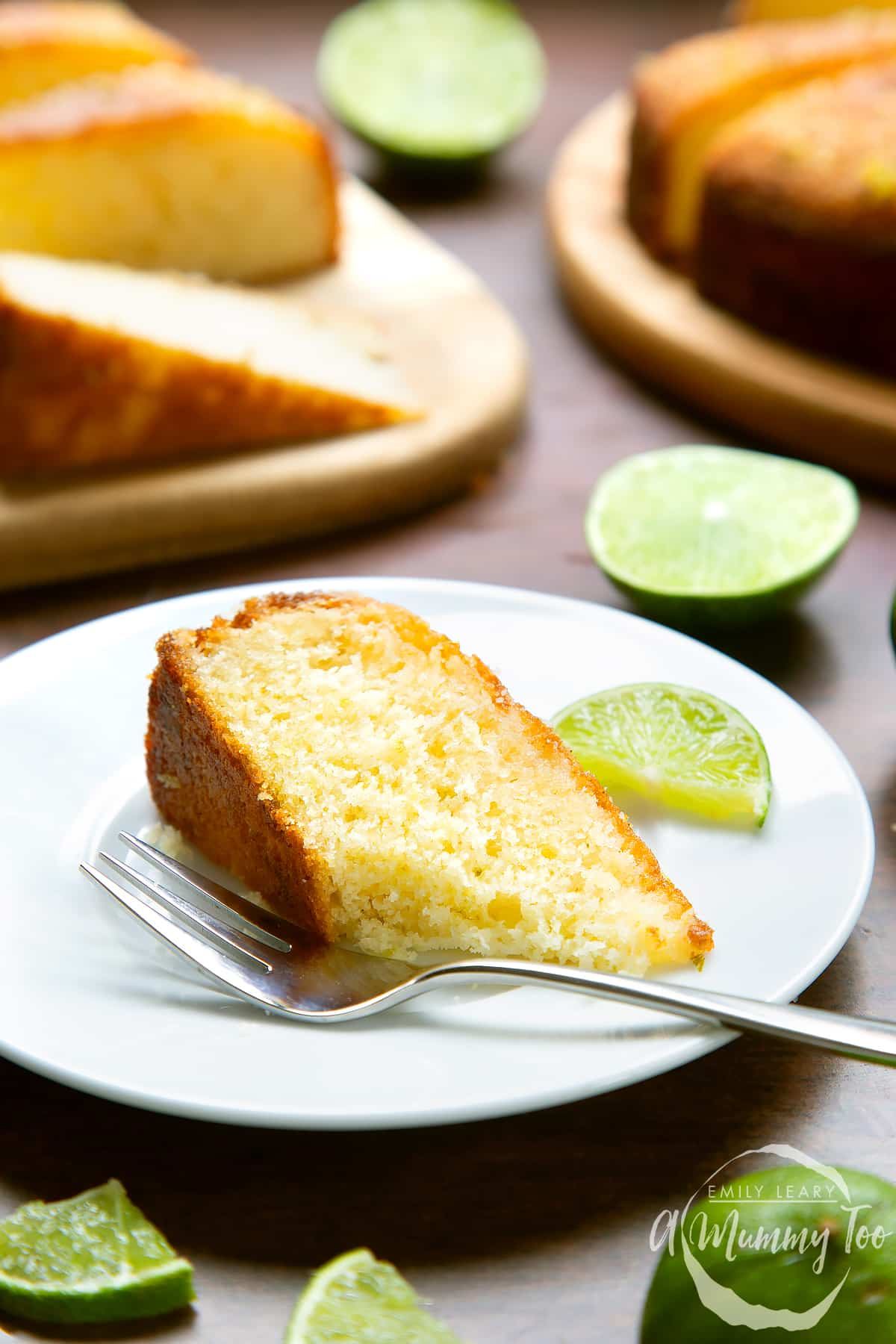 Slice of lime drizzle cake laying on a white plate with a fork. A piece has been eaten.
