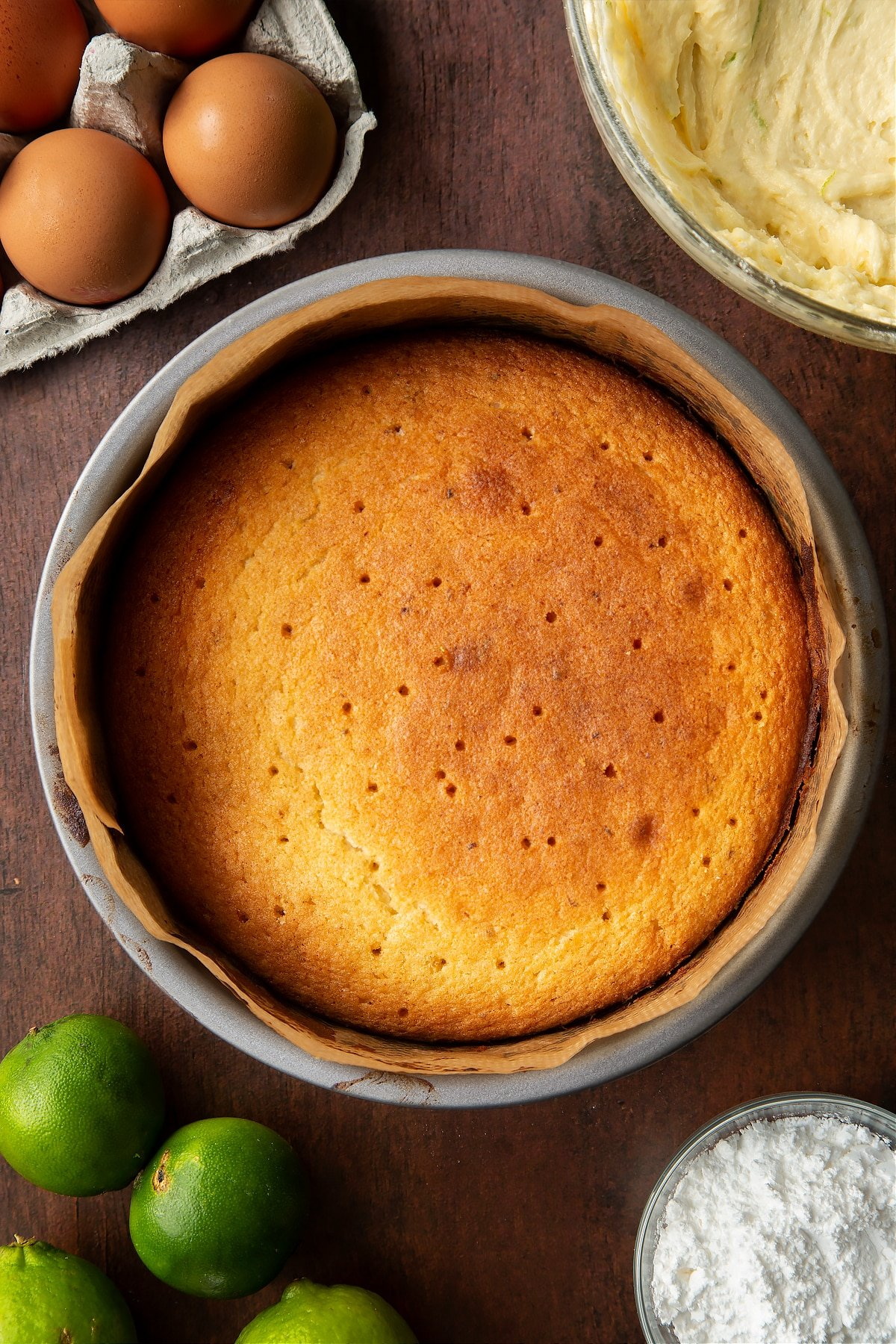 Baked lime drizzle cake in a lined cake tin with holes poked all over the surface. Ingredients to make lime drizzle cake surround the tin.