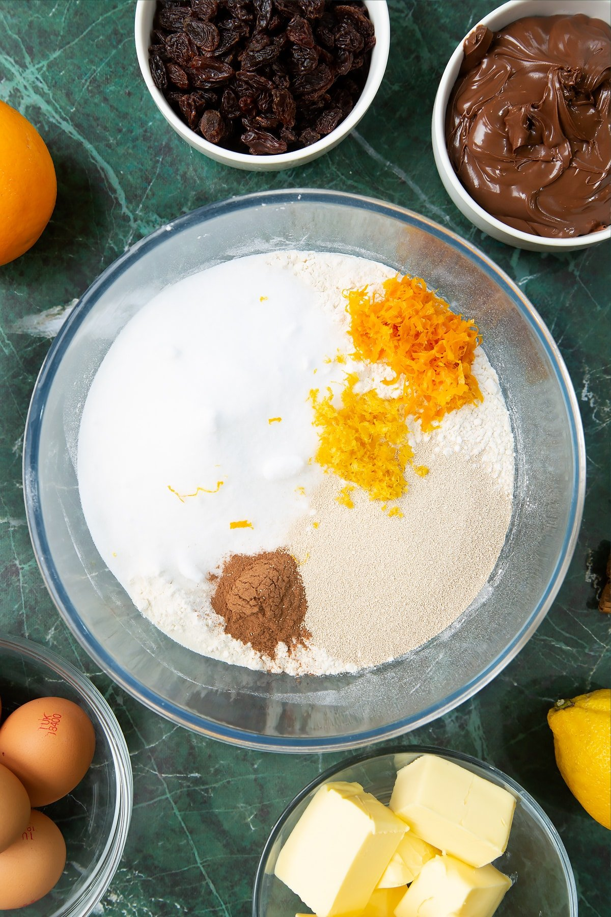 Bread flour, sugar, cinnamon, orange zest and lemon zest in a mixing bowl. Ingredients to make Nutella panettone surround the bowl.