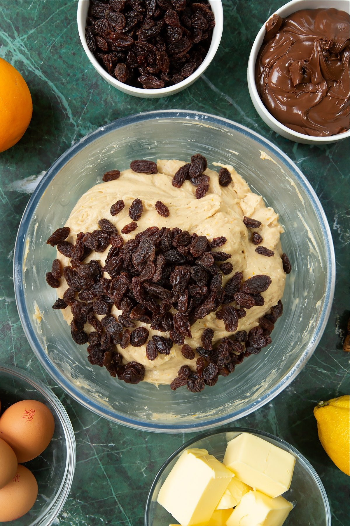 Spiced bread dough in a bowl with raisins on top. Ingredients to make Nutella panettone surround the bowl.