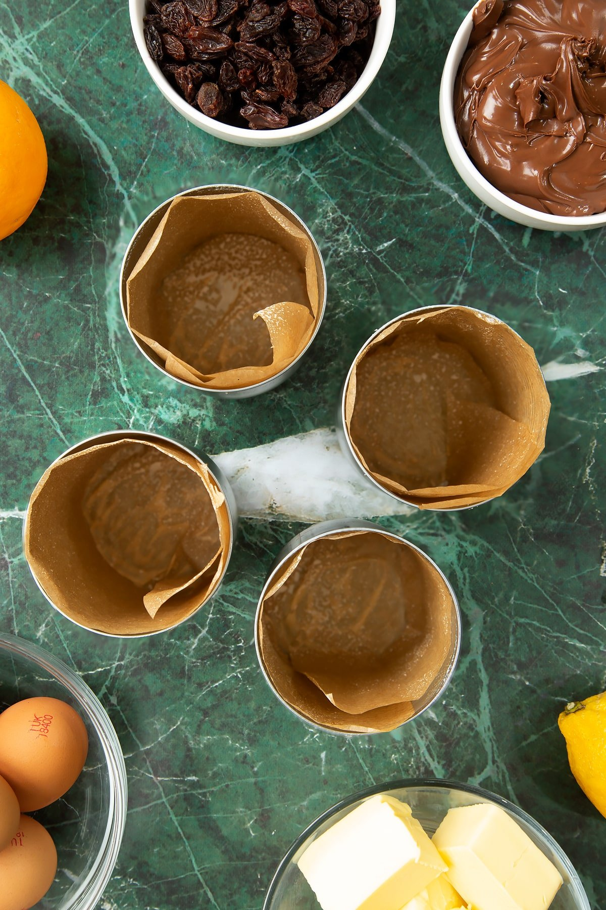 4 tin cans lined with brown baking paper. Ingredients to make Nutella panettone surround the cans.