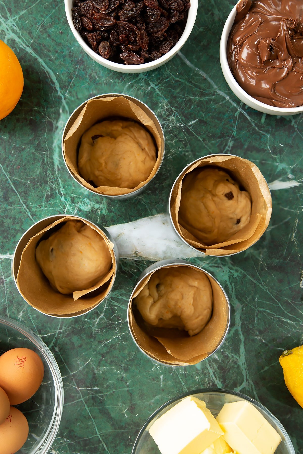 4 lined tin cans with a little dough at the bottom of eacch. Ingredients to make Nutella panettone surround the cans.