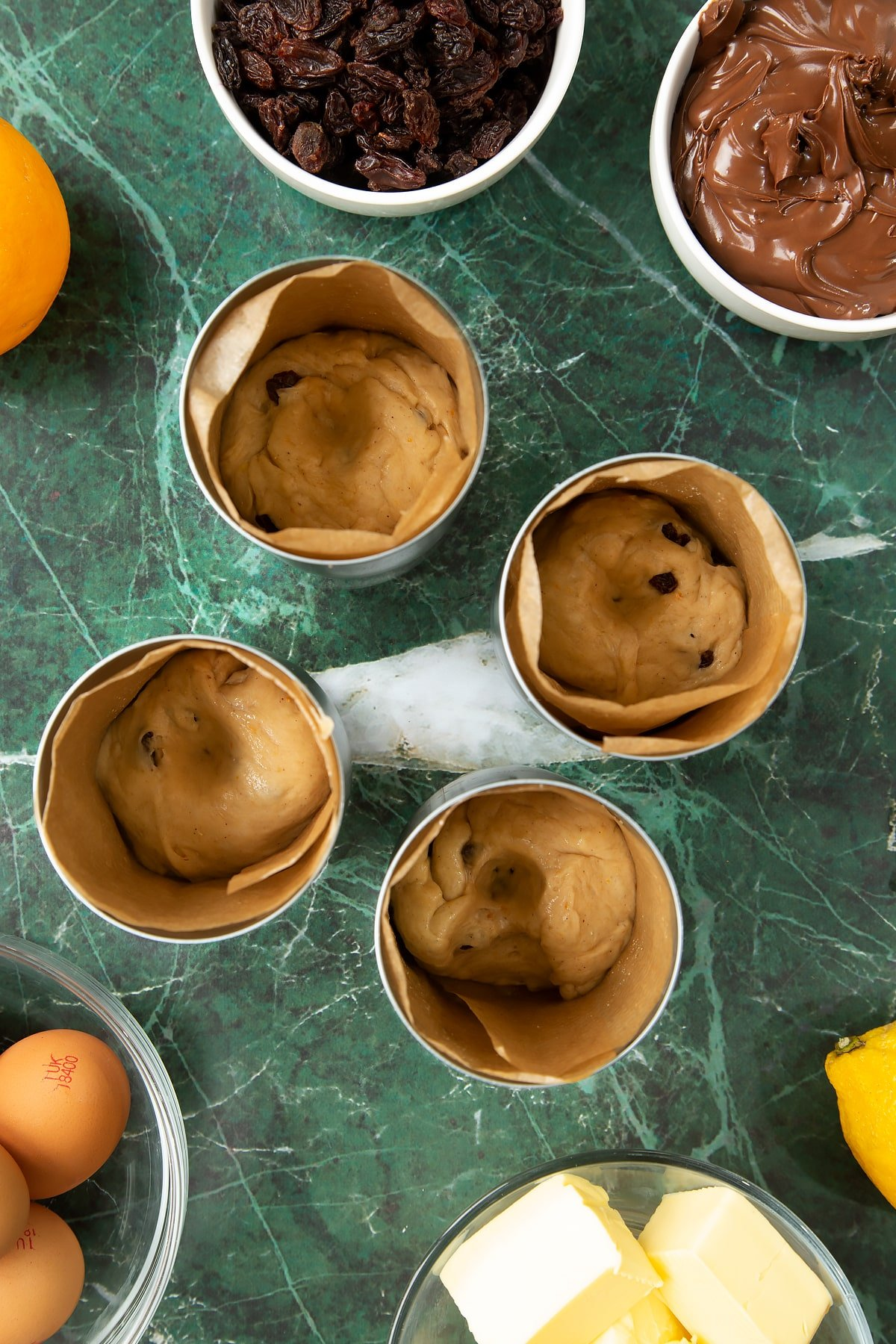 4 lined tin cans with a little dough at the bottom. Each has a well pushed into it. Ingredients to make Nutella panettone surround the cans.