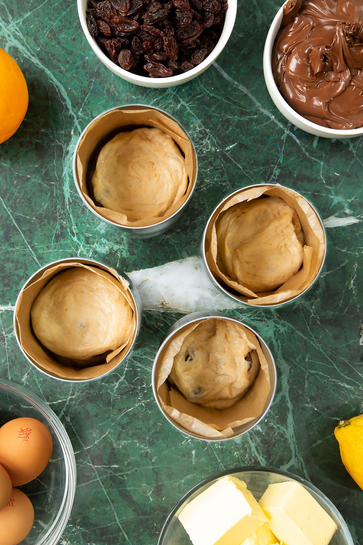 4 lined tin cans, each containing dough filled with Nutella. Ingredients to make Nutella panettone surround the cans.