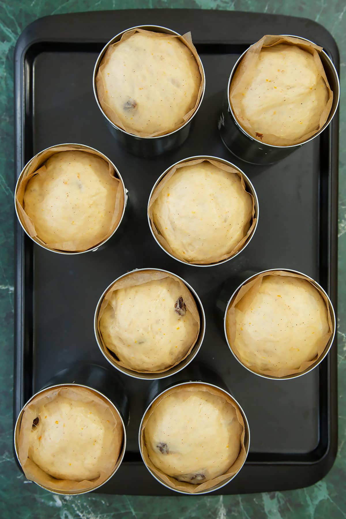 8 lined tin cans on a baking tray, each containing proved dough.