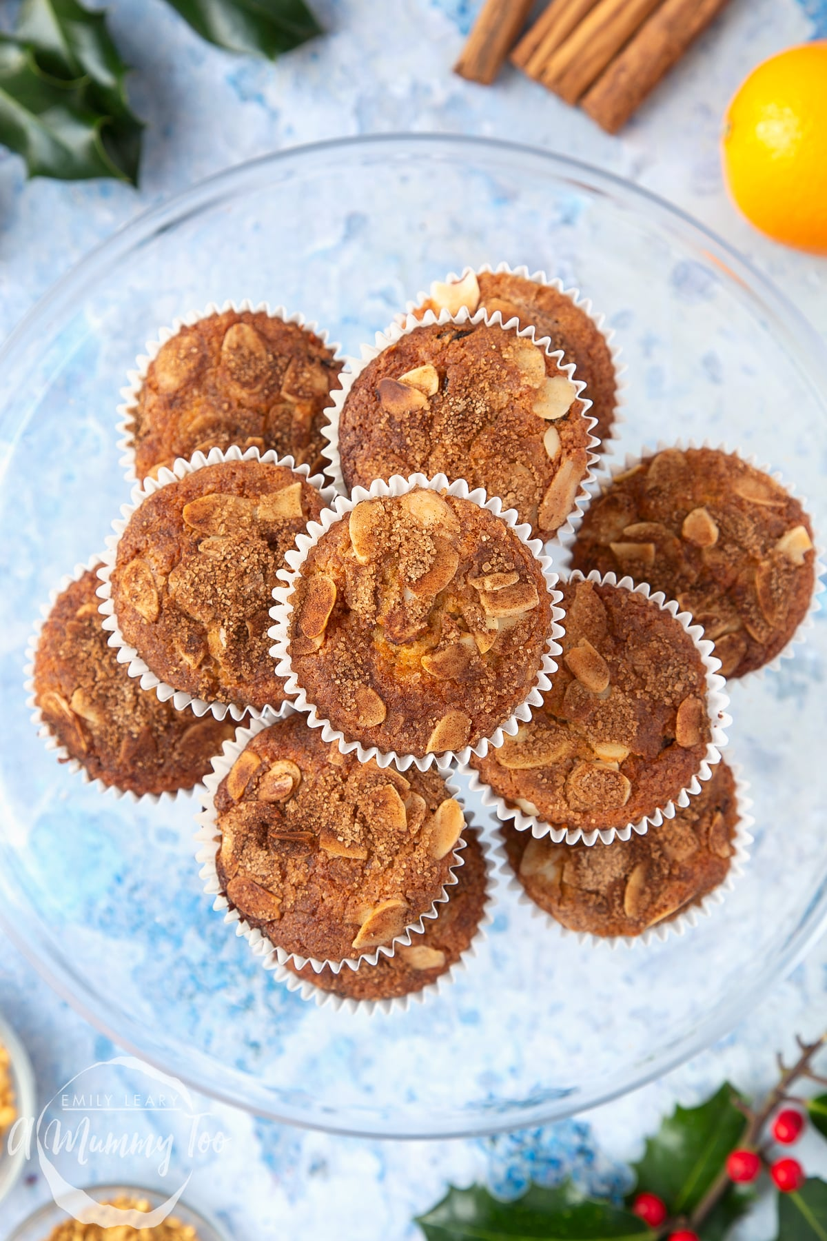Overhead shot of baked orange and cinnamon muffins stacked in a large clear bowl