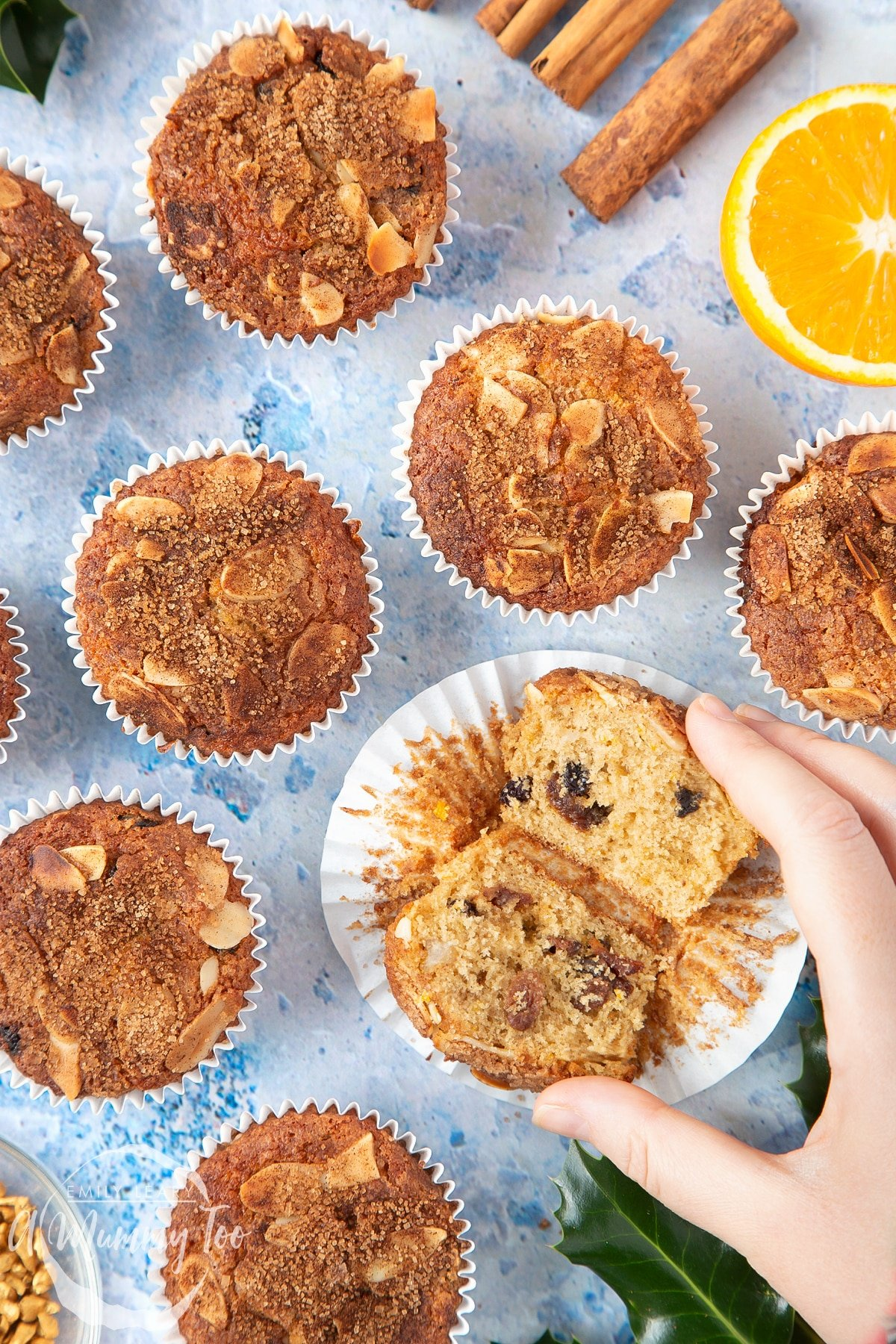 Overhead shot of a hand holding a Orange and cinnamon muffins with a mummy too logo in the lower-left corner