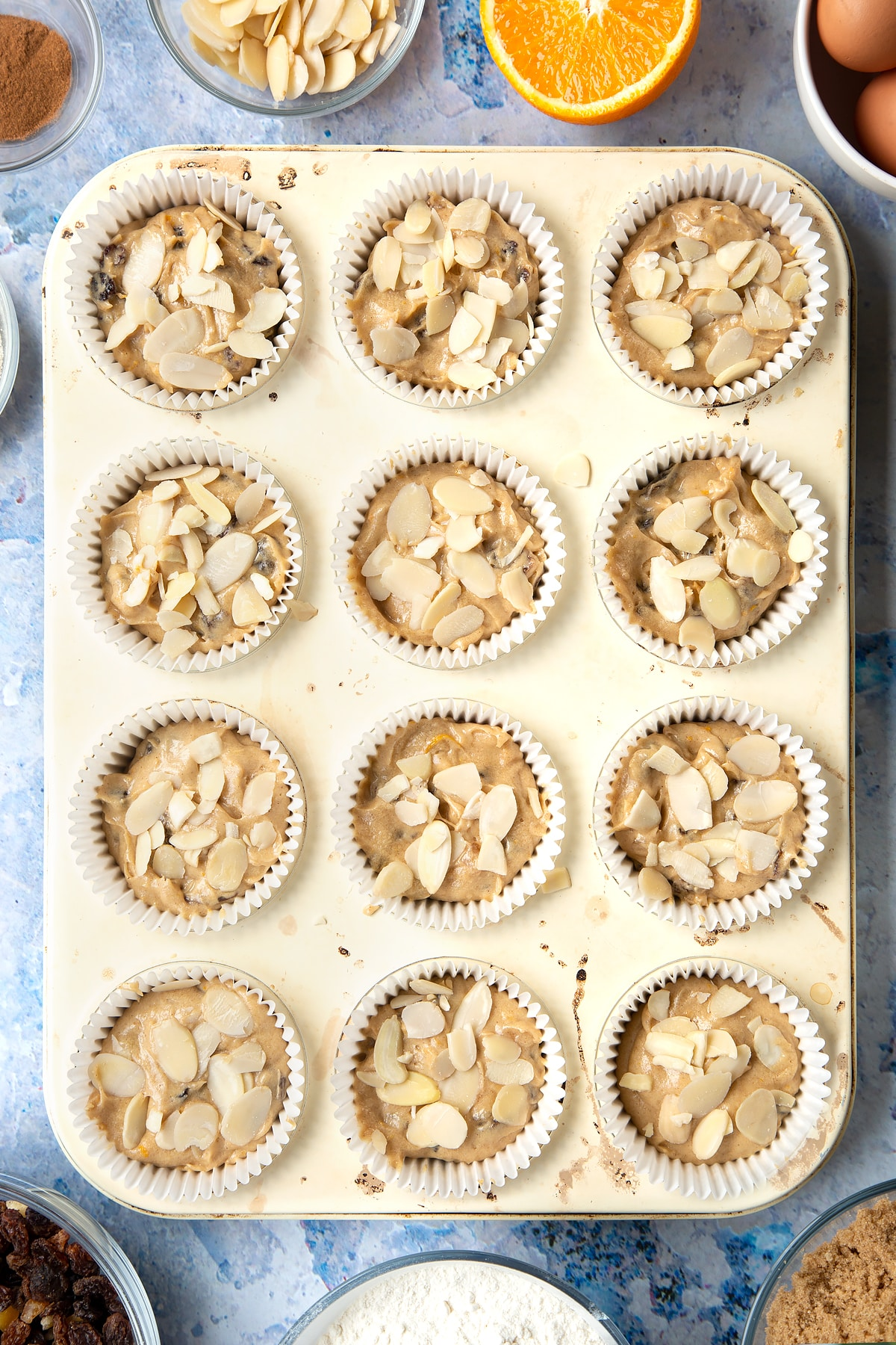 Overhead shot of orange and cinnamon muffin mix topped with flaked almonds in a muffin tray