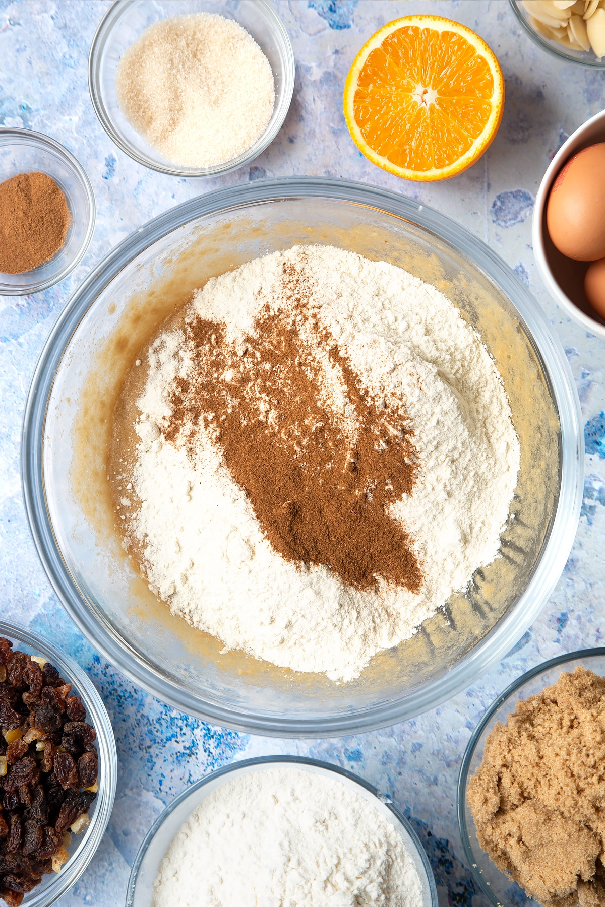 Overhead shot of flour and cinnamon in a large clear bowl