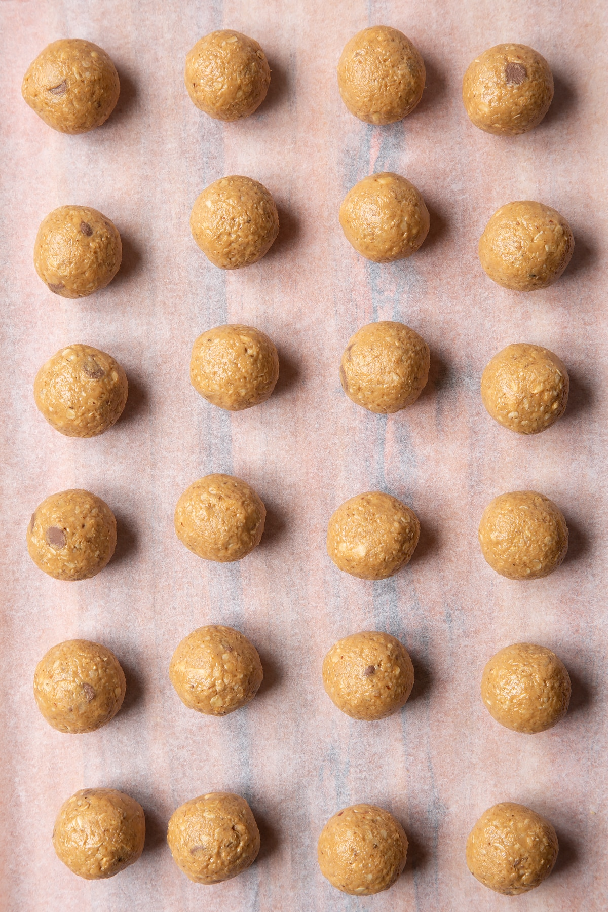 Peanut butter and oatmeal balls on a sheet of baking paper.