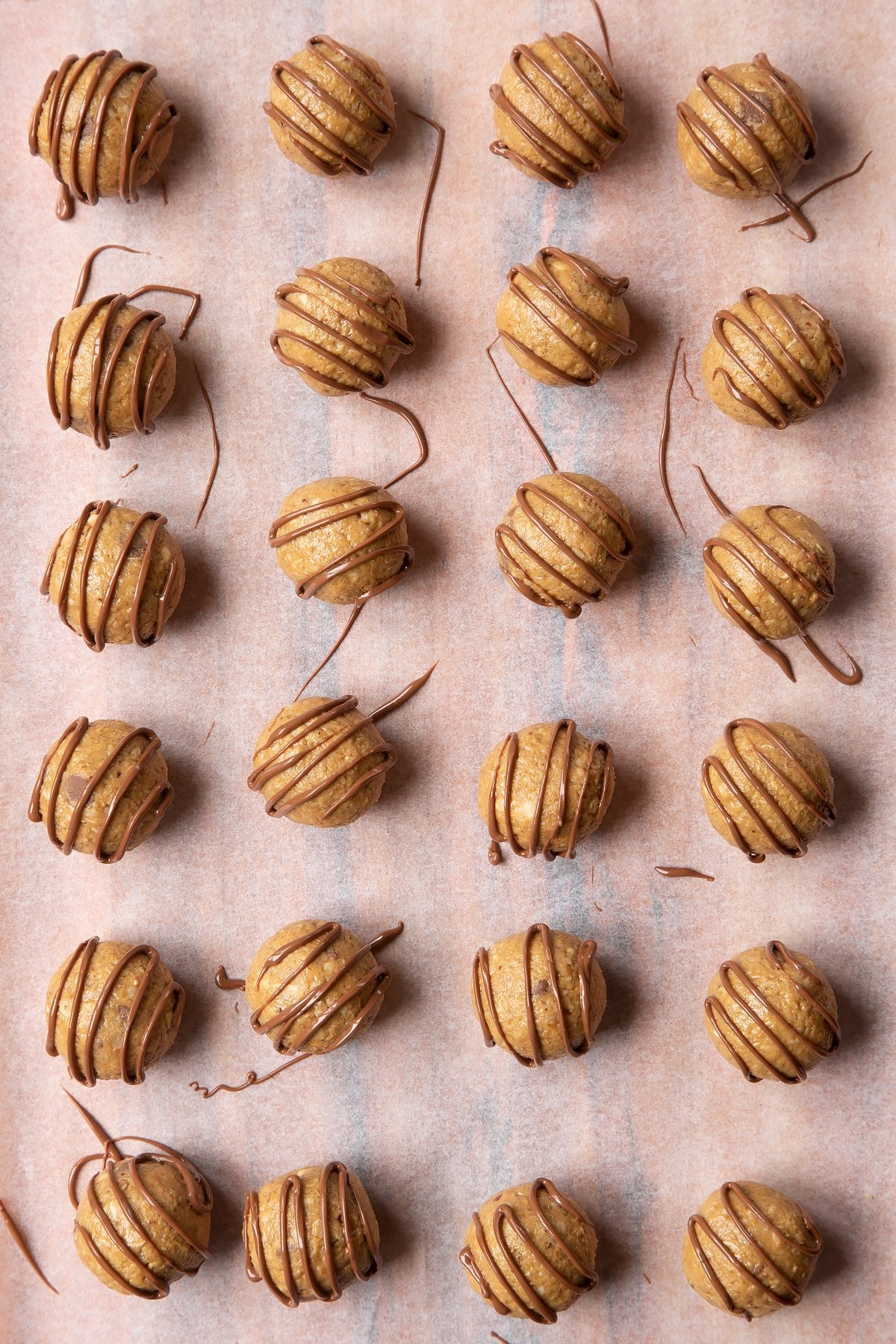 Peanut butter and oatmeal balls decorated with chocolate on a sheet of baking paper.