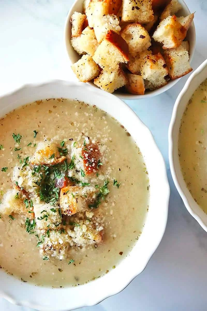 Close up of Garlic Bread Soup in a white decorative bowl. A bowl of the croutons to the side.