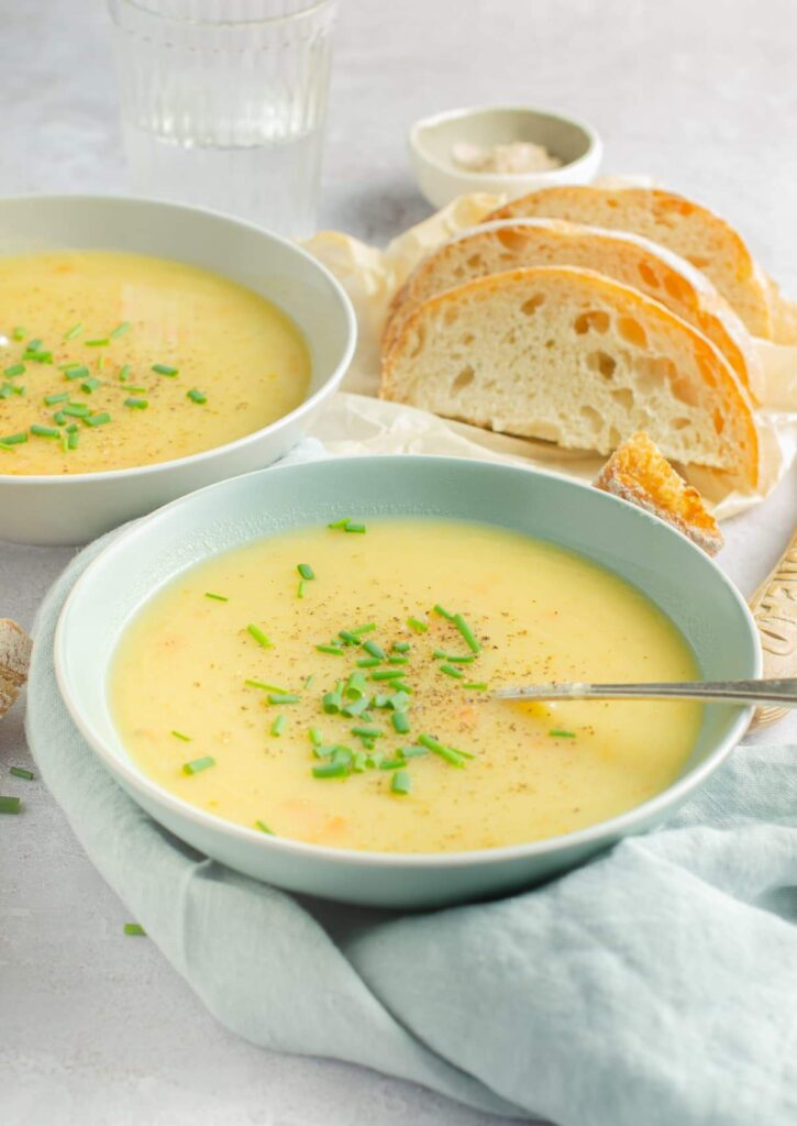 Two bowls of leek and potato soup sit on top of a silver table top surrounded by chunks of bread roll.