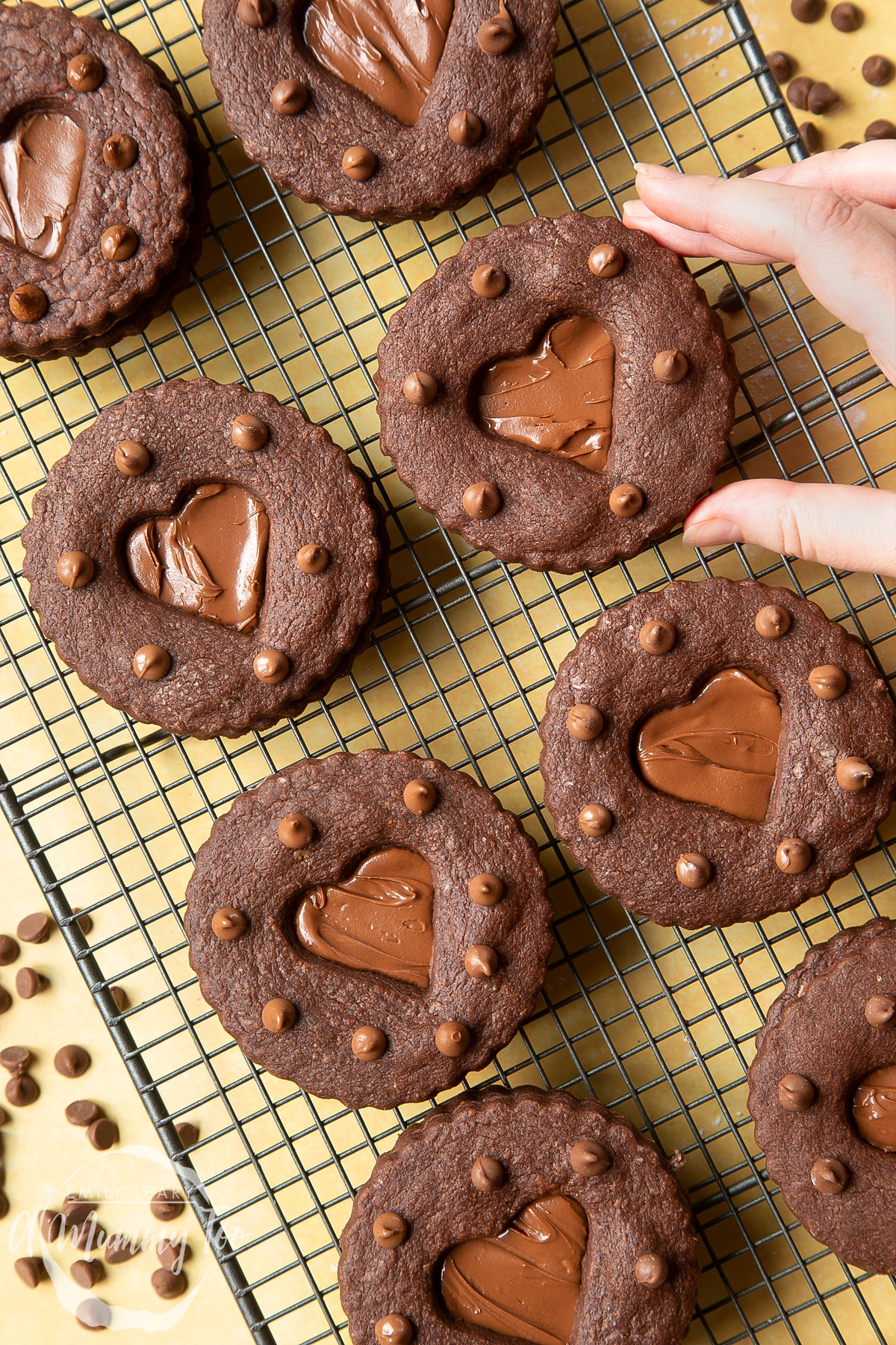 Nutella sandwich cookies on a cooling rack. A hand reaches to take one.