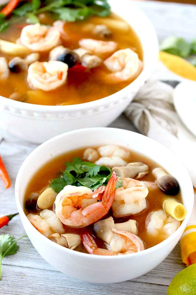 Close up of a white bowl filled with Tom Yum Soup also known as Hot and Sour Soup.