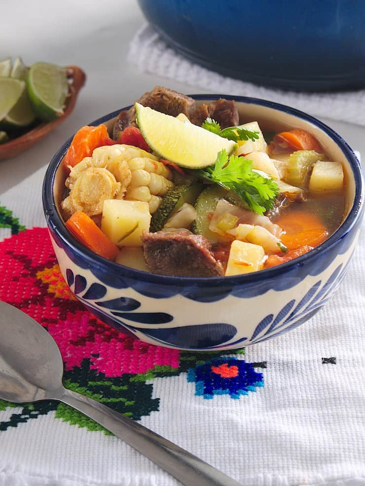 Blue and white decorative bowl filled with Caldo de Res (Beef Soup). In the corner there's a plate of cut up limes and a colourful napkin.