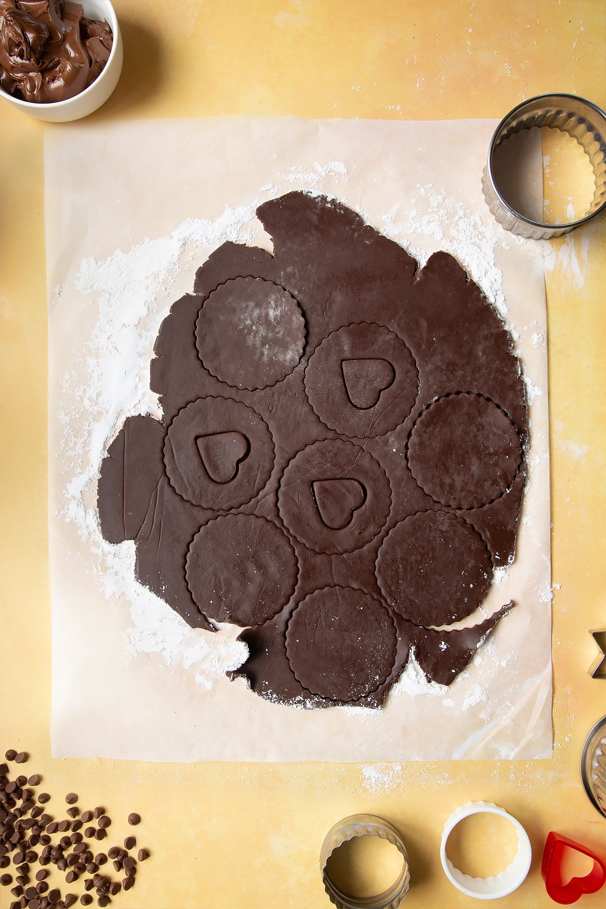 Chocolate shortbread dough rolled out on baking paper. Cookie shapes have been cut out, including heart shapes in the centre of some of the discs.