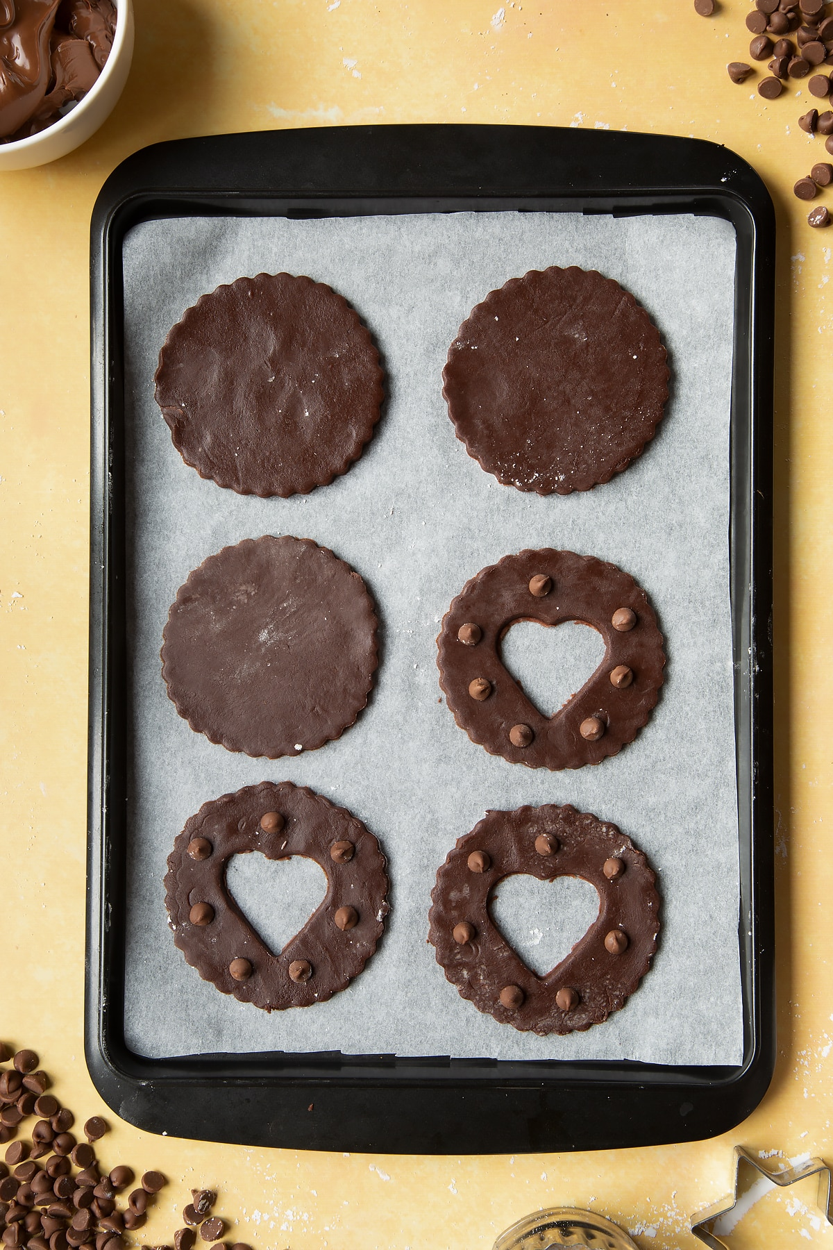 Raw chocolate sandwich cookies on a tray lined with baking paper.
