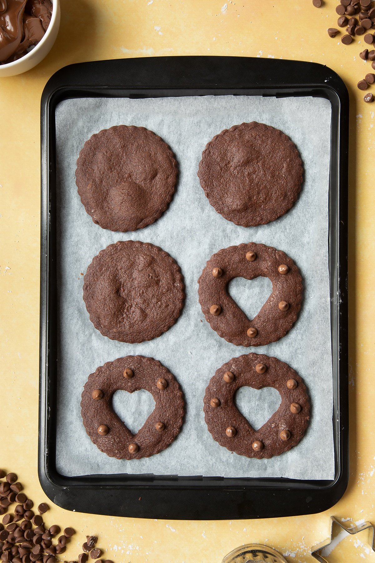 Freshly baked chocolate sandwich cookies on a tray lined with baking paper.