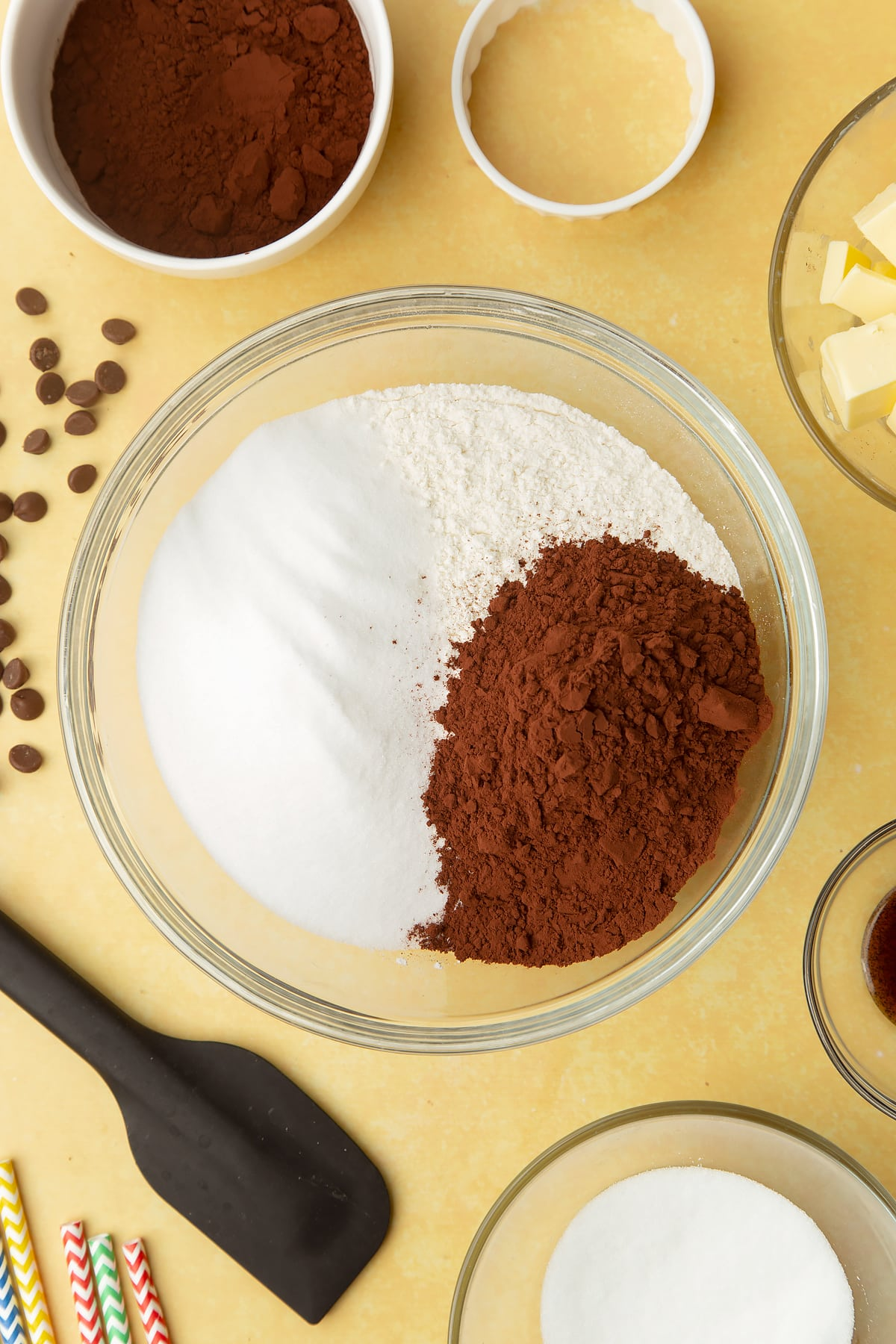 Cocoa, sugar and flour in a bowl. Ingredients to make Nutella sandwich cookies surround the bowl.