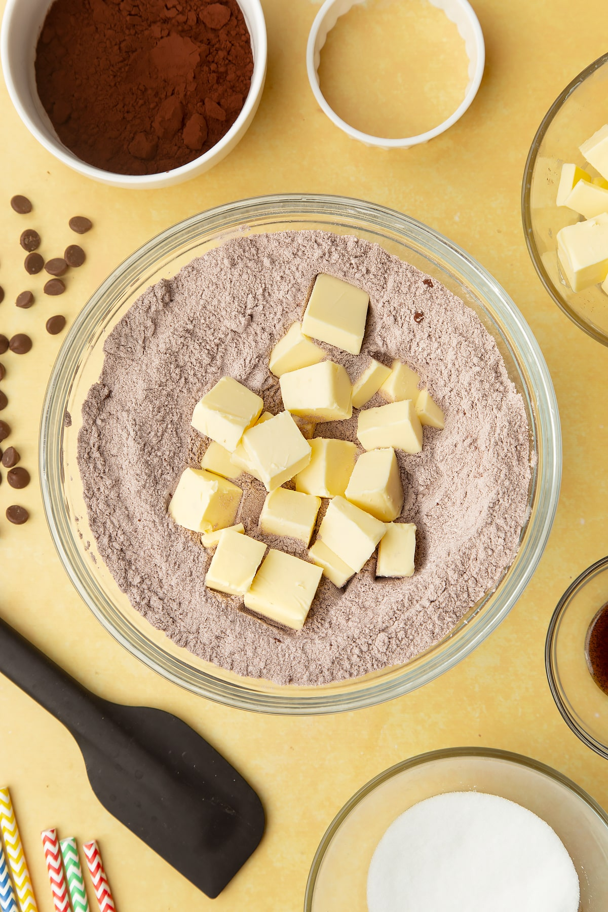 Cocoa, sugar, flour with cubed butter on top in a bowl. Ingredients to make Nutella sandwich cookies surround the bowl.