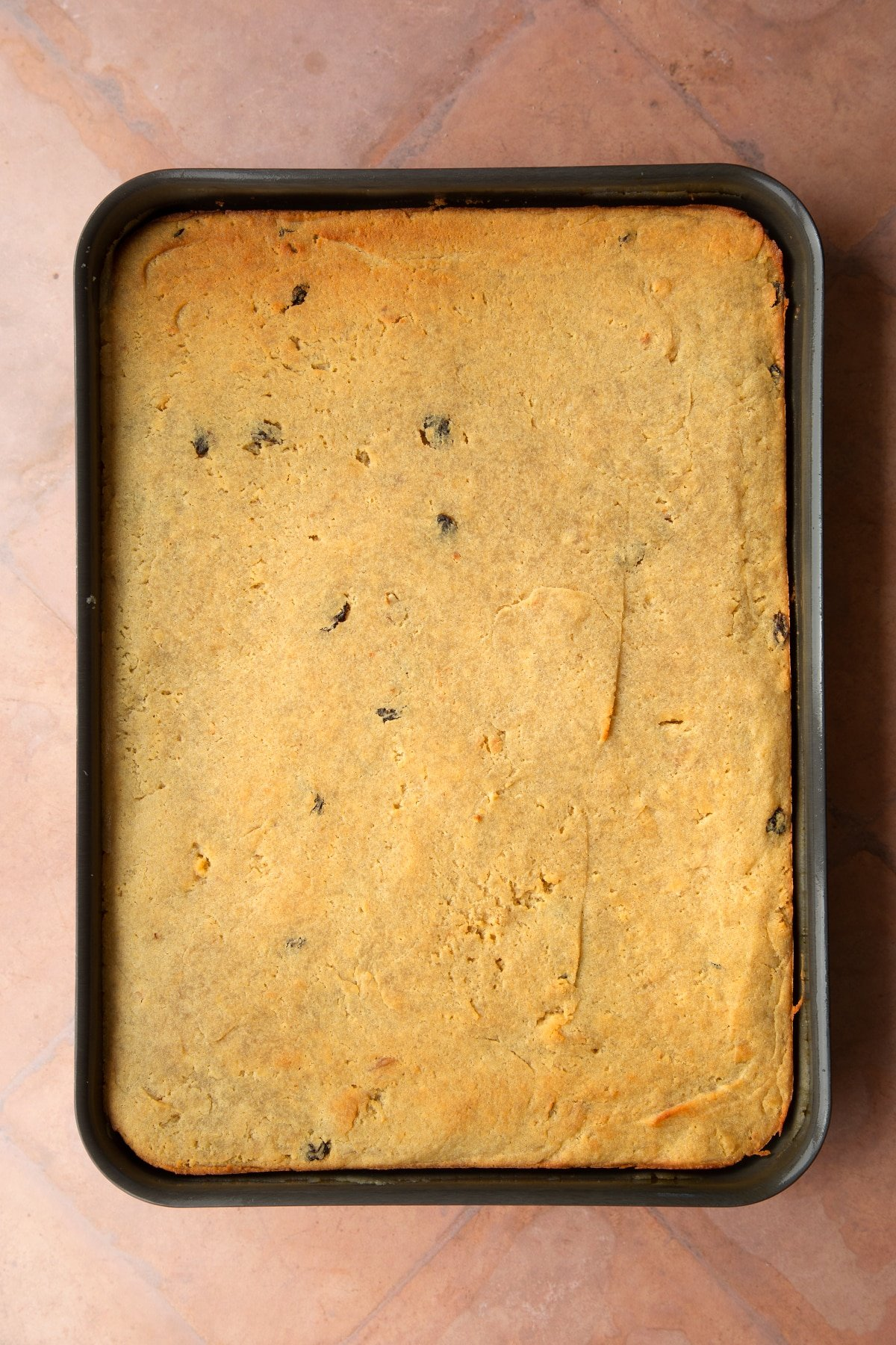 A greased tray filled with freshly baked golden semolina cake.