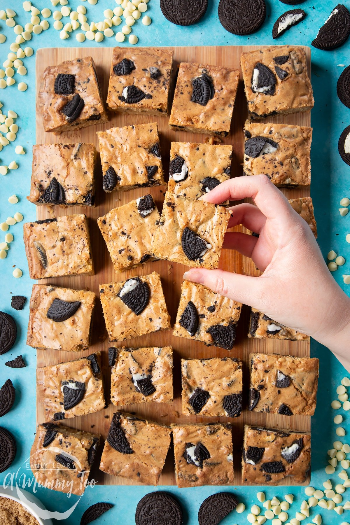 Overhead shot of a hand holding an Oreo Blondie over a wooden board of Oreo Blondies