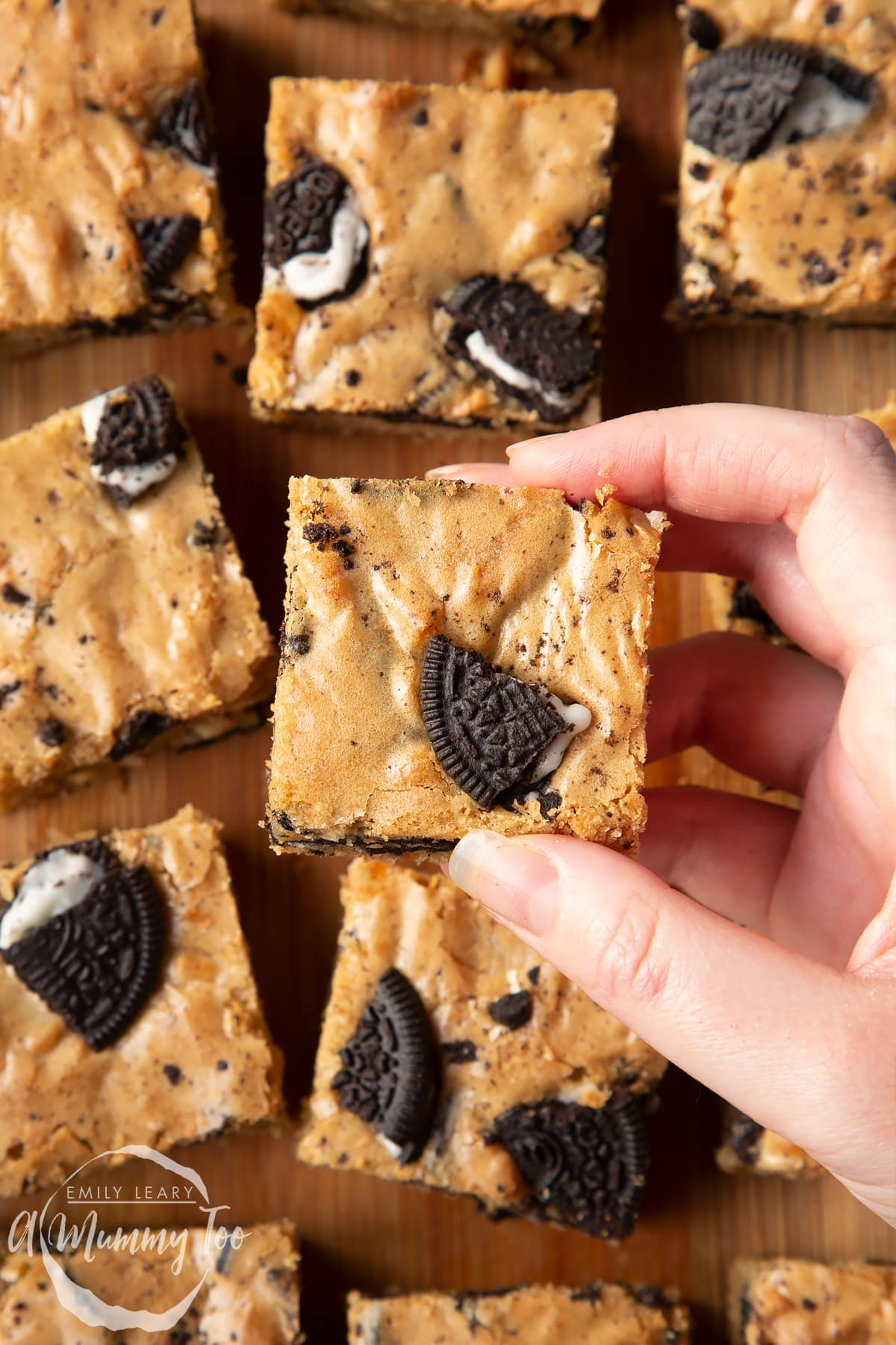Overhead shot of a hand holding a square Oreo Blondie over a wooden tray