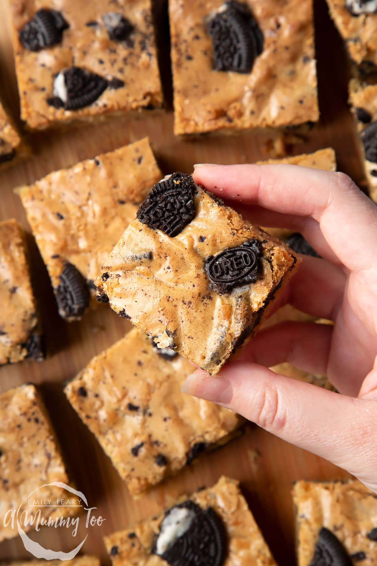 Overhead shot of a hand holding a square Oreo Blondie over a wooden board