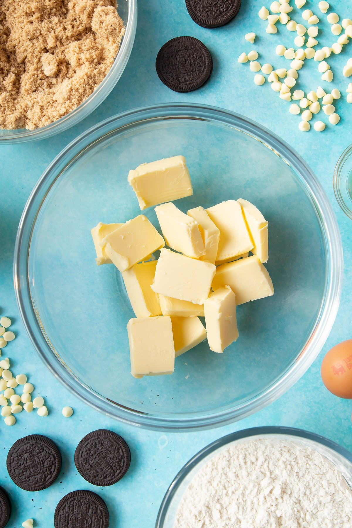 Overhead shot of butter chunks in a large clear bowl