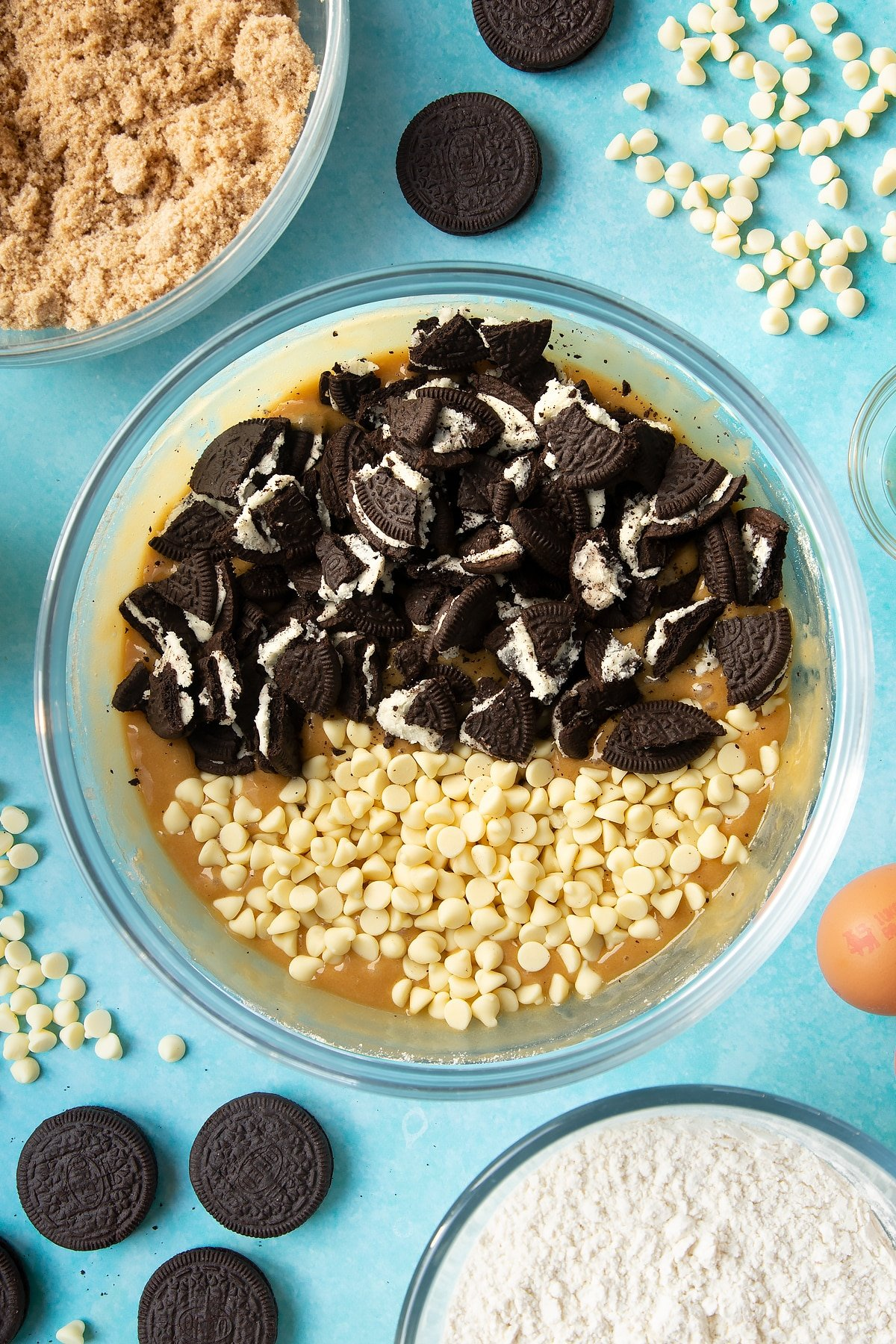 Overhead shot of blondies mix with chopped Oreo cookies in a large clear bowl