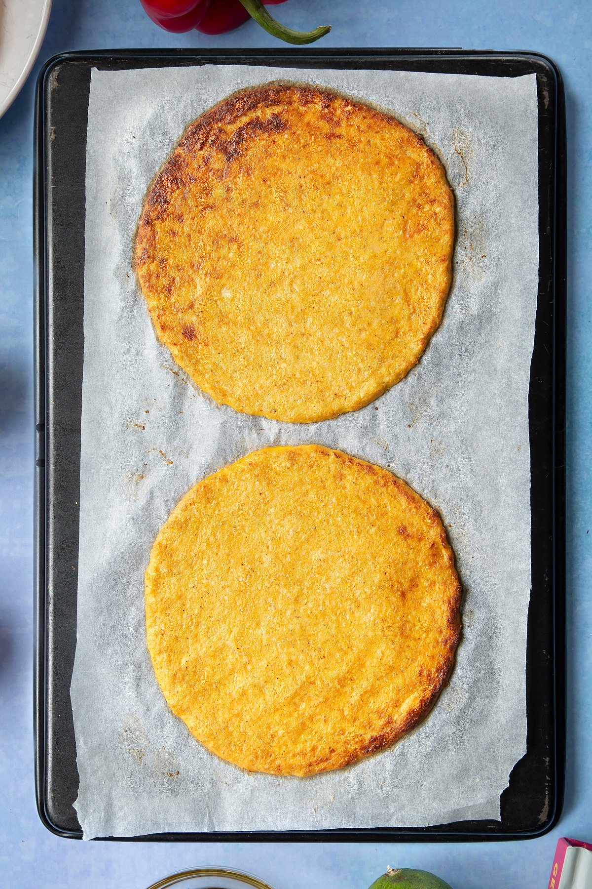 Cauliflower tortillas on a lined baking tray.