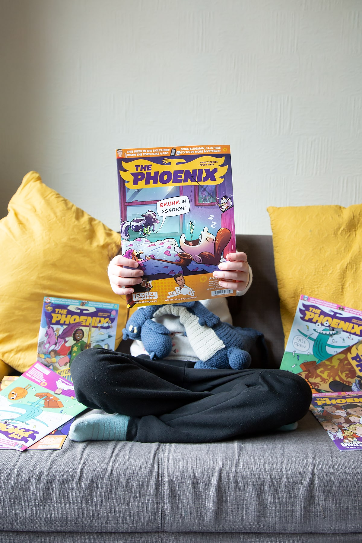 A child sitting on a sofa holding The Phoenix magazine outwards towards the camera