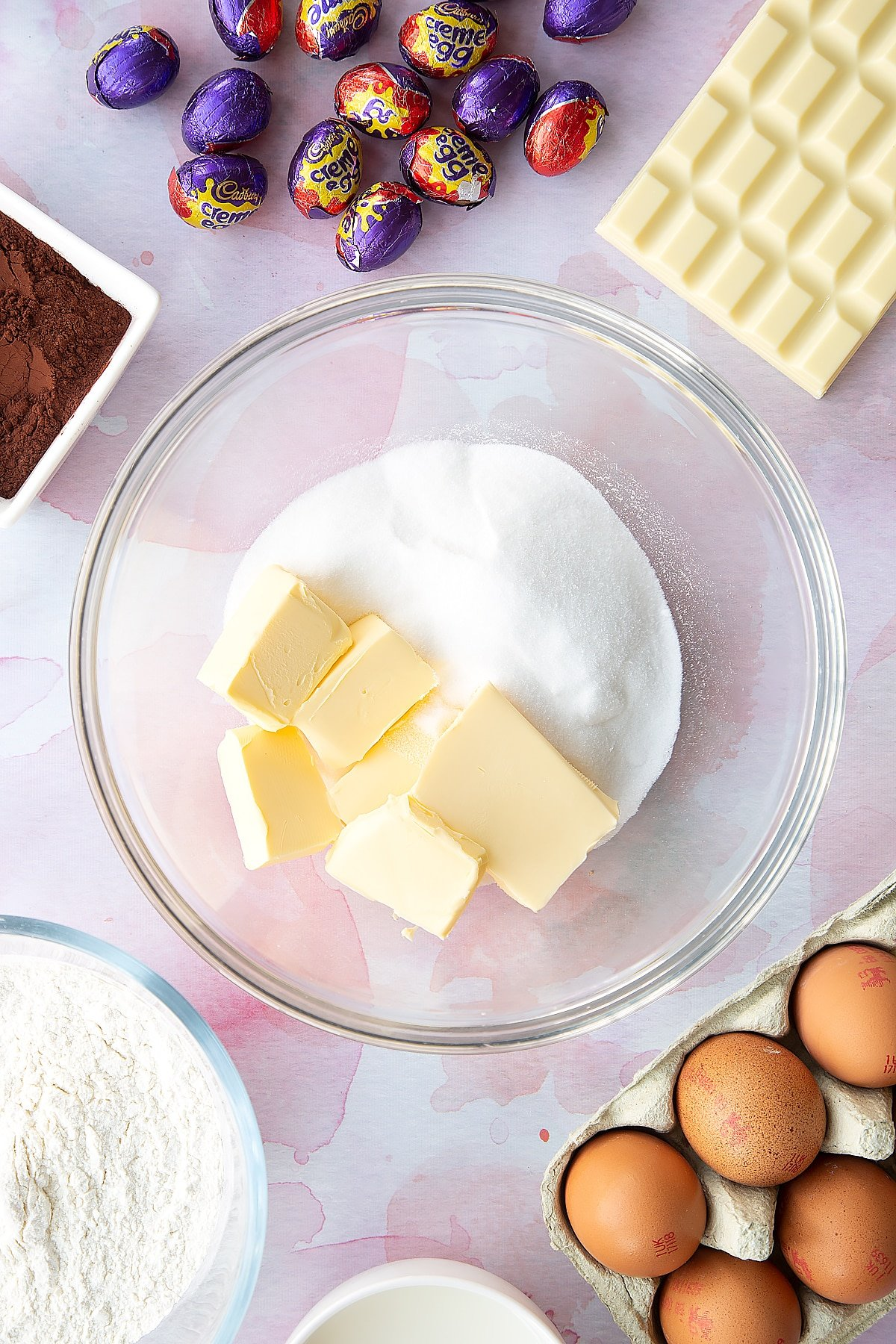 Butter and sugar in a bowl. Ingredients to make Cadbury Creme Egg cakes surround the bowl.