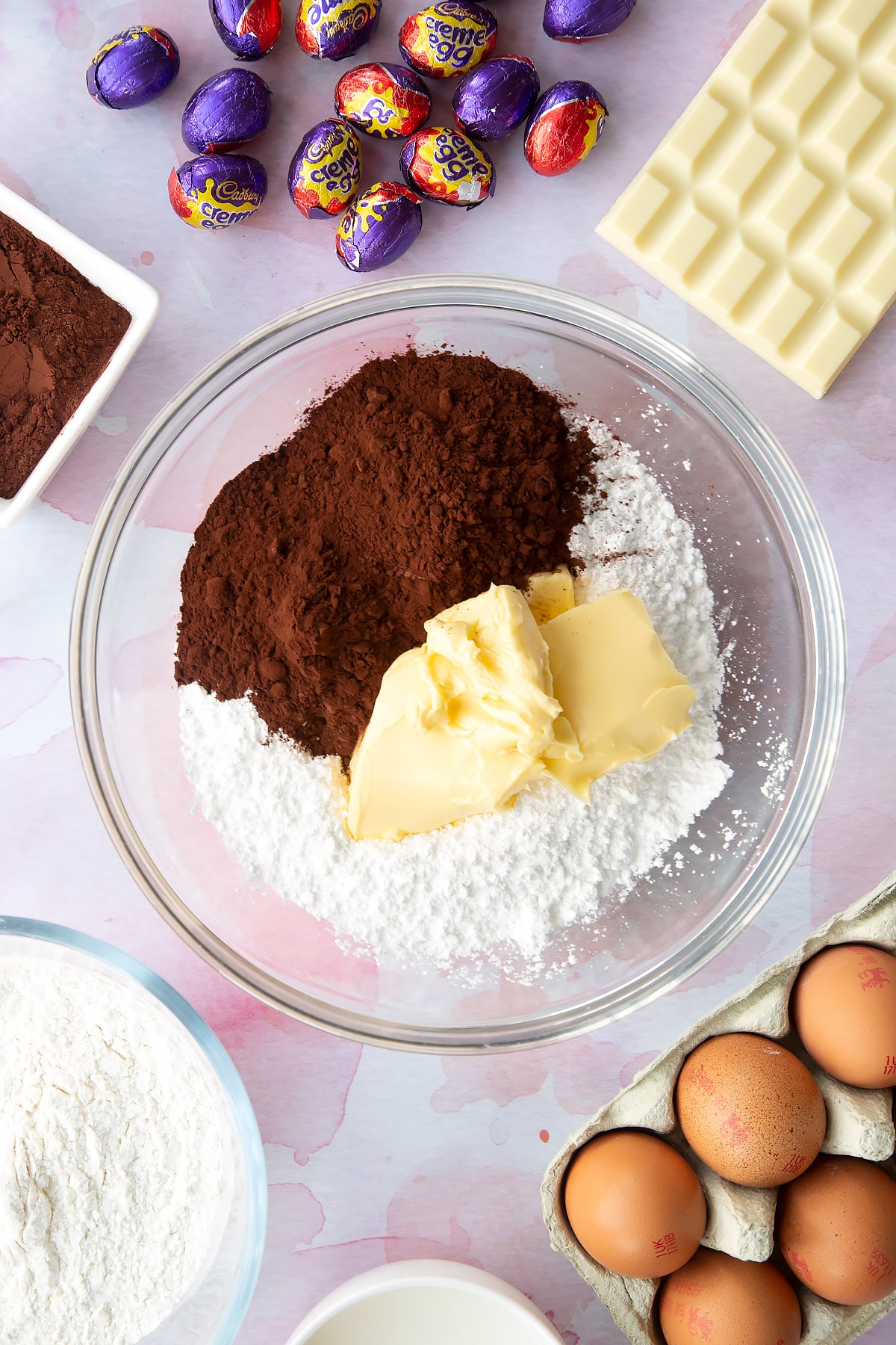 Butter, icing sugar, cocoa powder and water in a bowl. Ingredients to make Cadbury Creme Egg cakes surround the bowl.