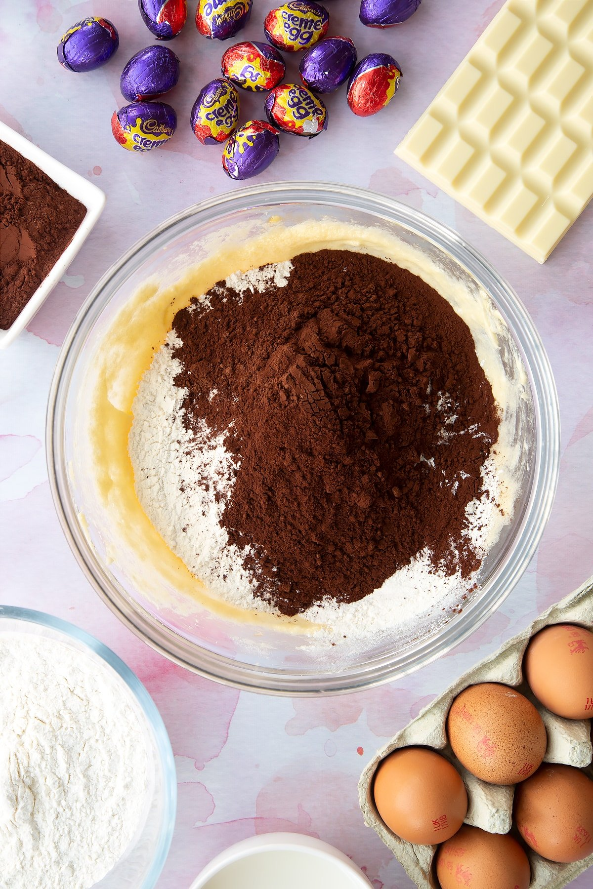 Butter, sugar and eggs beaten together with cocoa, self-raising flour and baking powder on top. Ingredients to make Cadbury Creme Egg cakes surround the bowl.