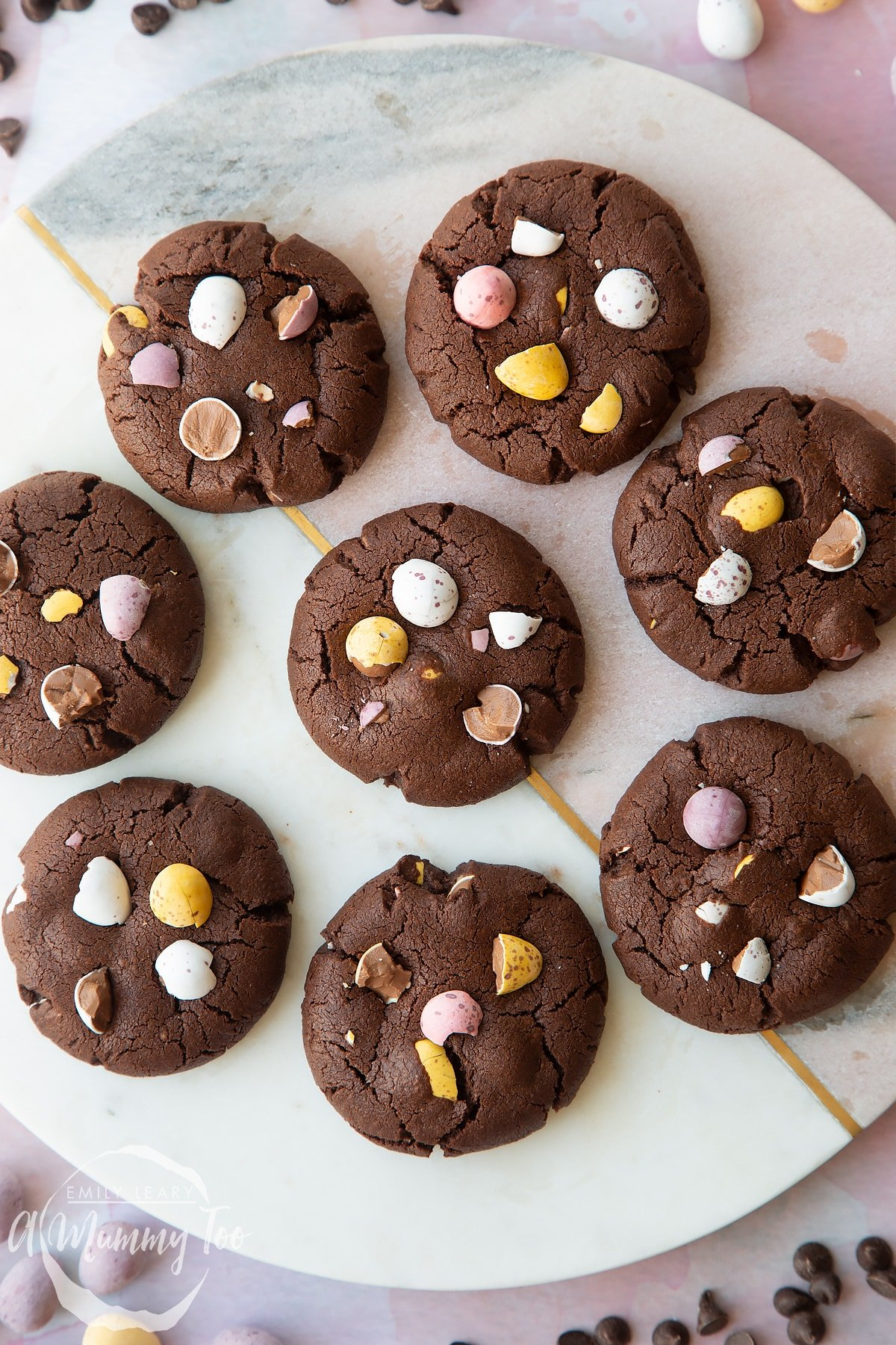Chocolate Easter cookies arranged on a round marble board. The cookies are chocolate brown and topped with Mini Eggs.