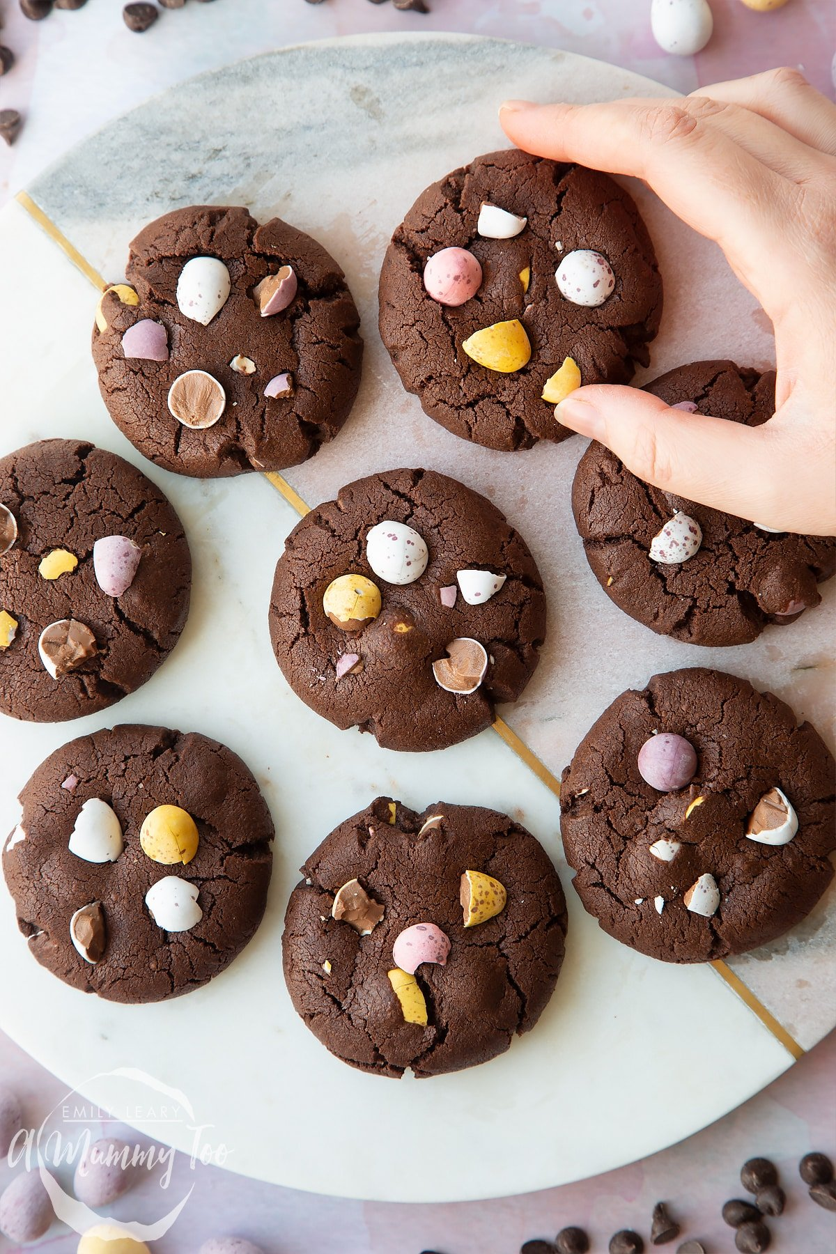 Chocolate Easter cookies arranged on a round marble board. The cookies are chocolate brown and topped with Mini Eggs. A hand reaches for one.