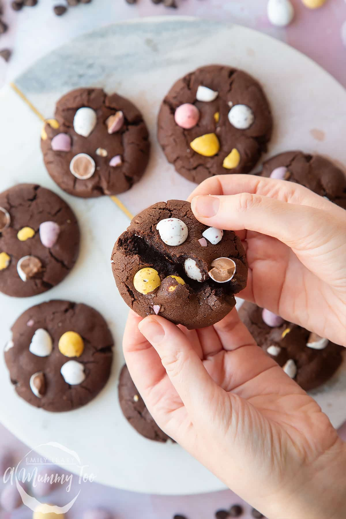 Hands breaking open a chocolate Easter cookie, with more arranged on a round marble board. The cookies are chocolate brown and topped with Mini Eggs.