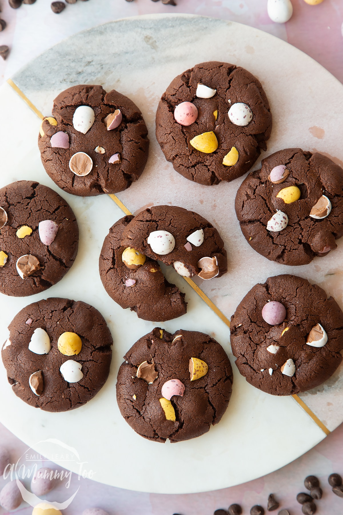 Chocolate Easter cookies arranged on a round marble board. One is broken in half.