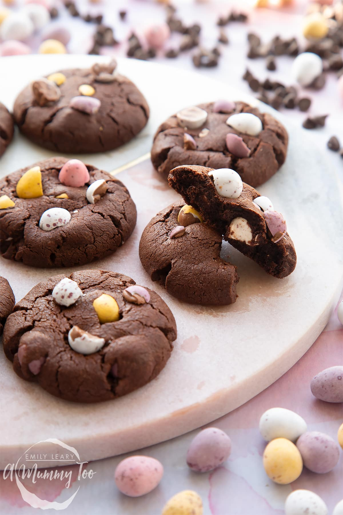 Chocolate Easter cookies arranged on a round marble board. The board is surrounded by Mini Eggs.