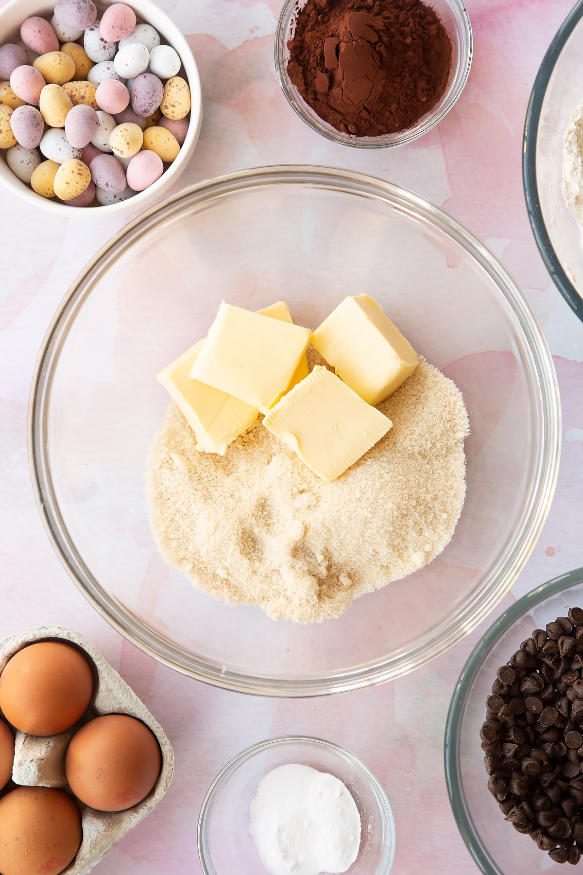Butter and golden granulated sugar in a bowl. Ingredients to make Chocolate Easter cookies surround the bowl.