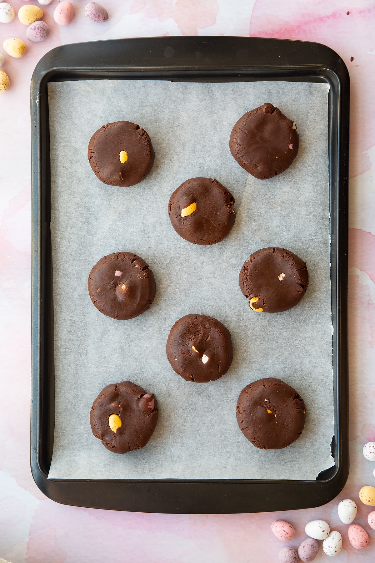 Chocolate Easter cookie dough discs on a tray lined with baking paper.