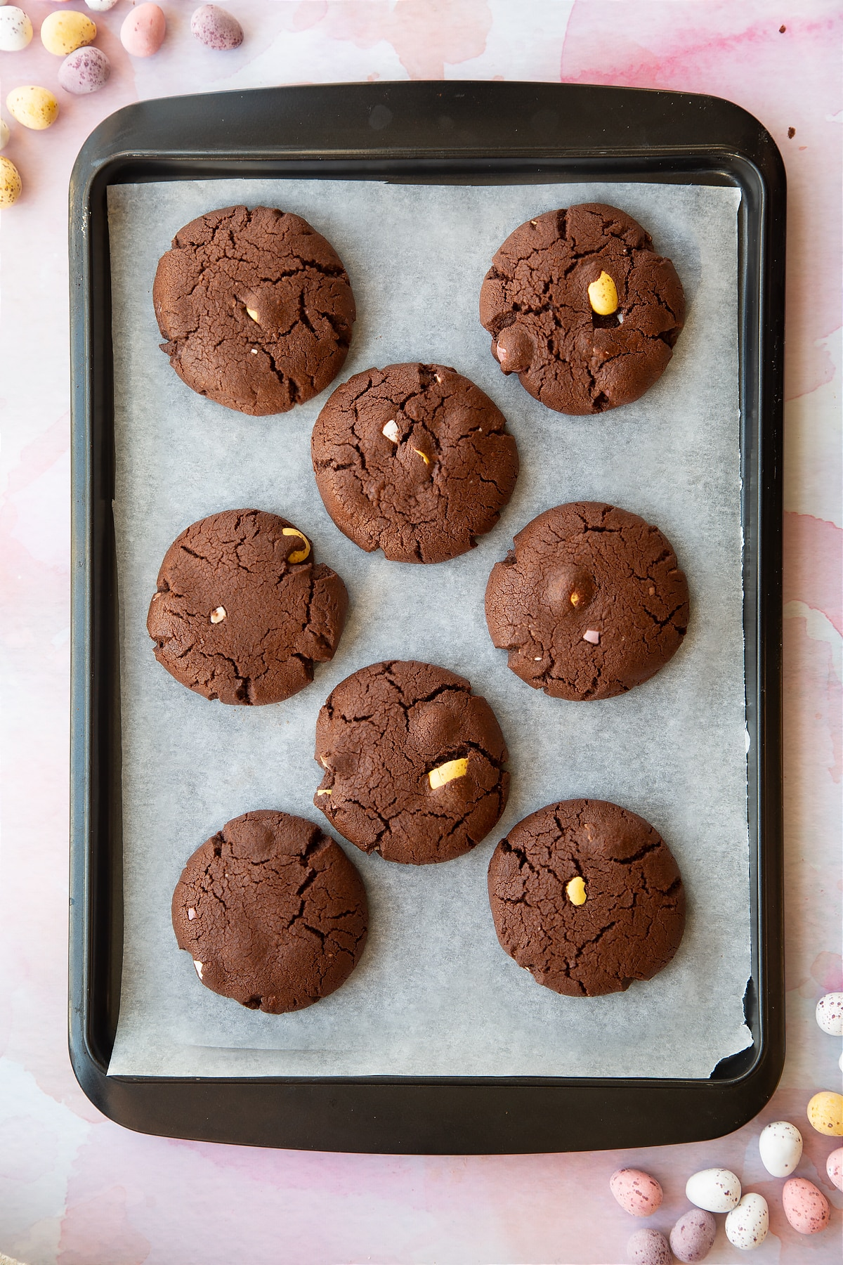 Chocolate Easter cookies on a tray lined with baking paper.