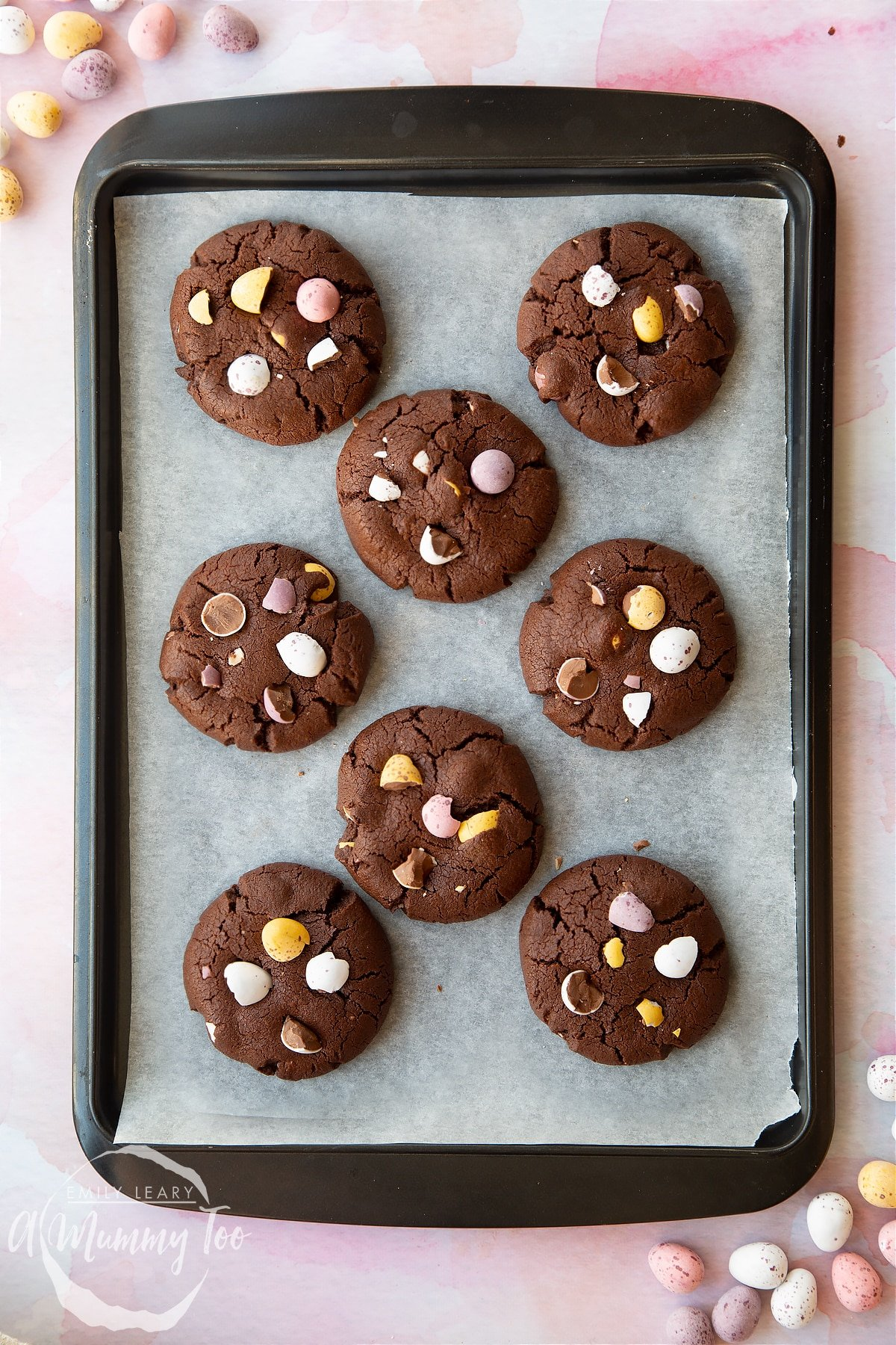 Chocolate Easter cookies arranged on a baking tray. The cookies are chocolate brown and topped with Mini Eggs.