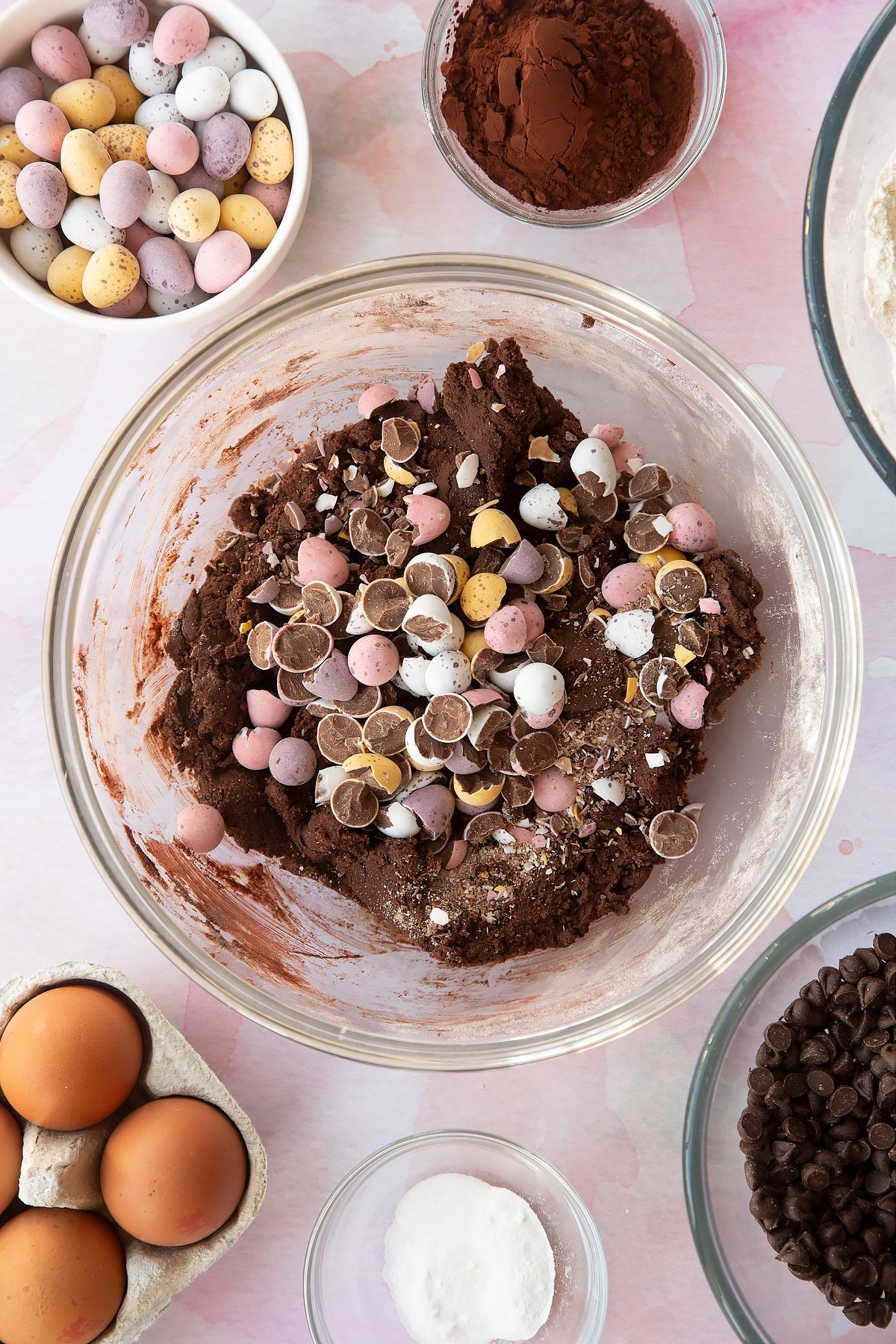 Chocolate cookie dough in a bowl with smashed Mini Eggs on top. Ingredients to make Chocolate Easter cookies surround the bowl.